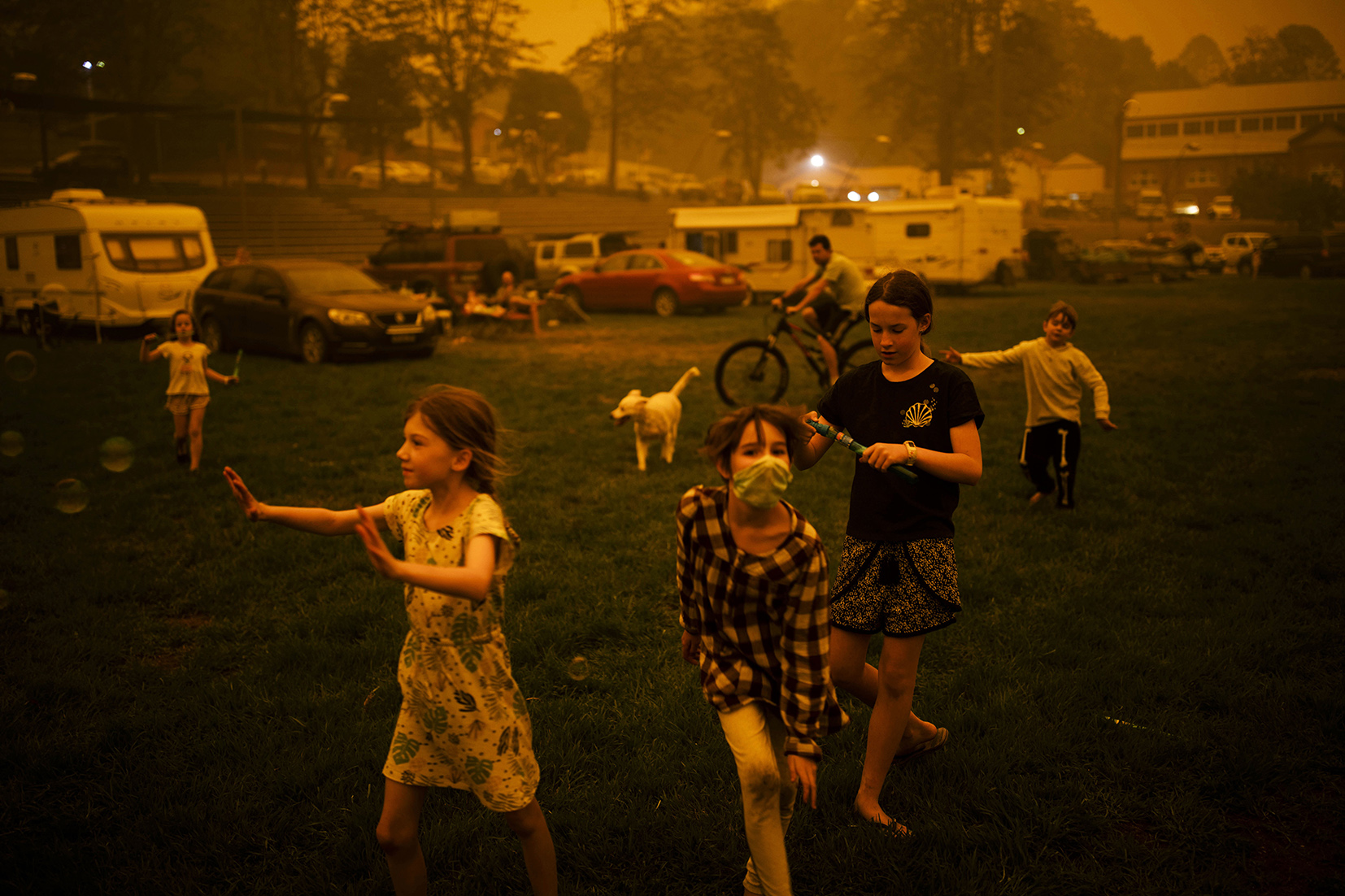 Photograph featuring children playing on a sports field. One wears a face mask. The sky and light are tinged orange with smoke.