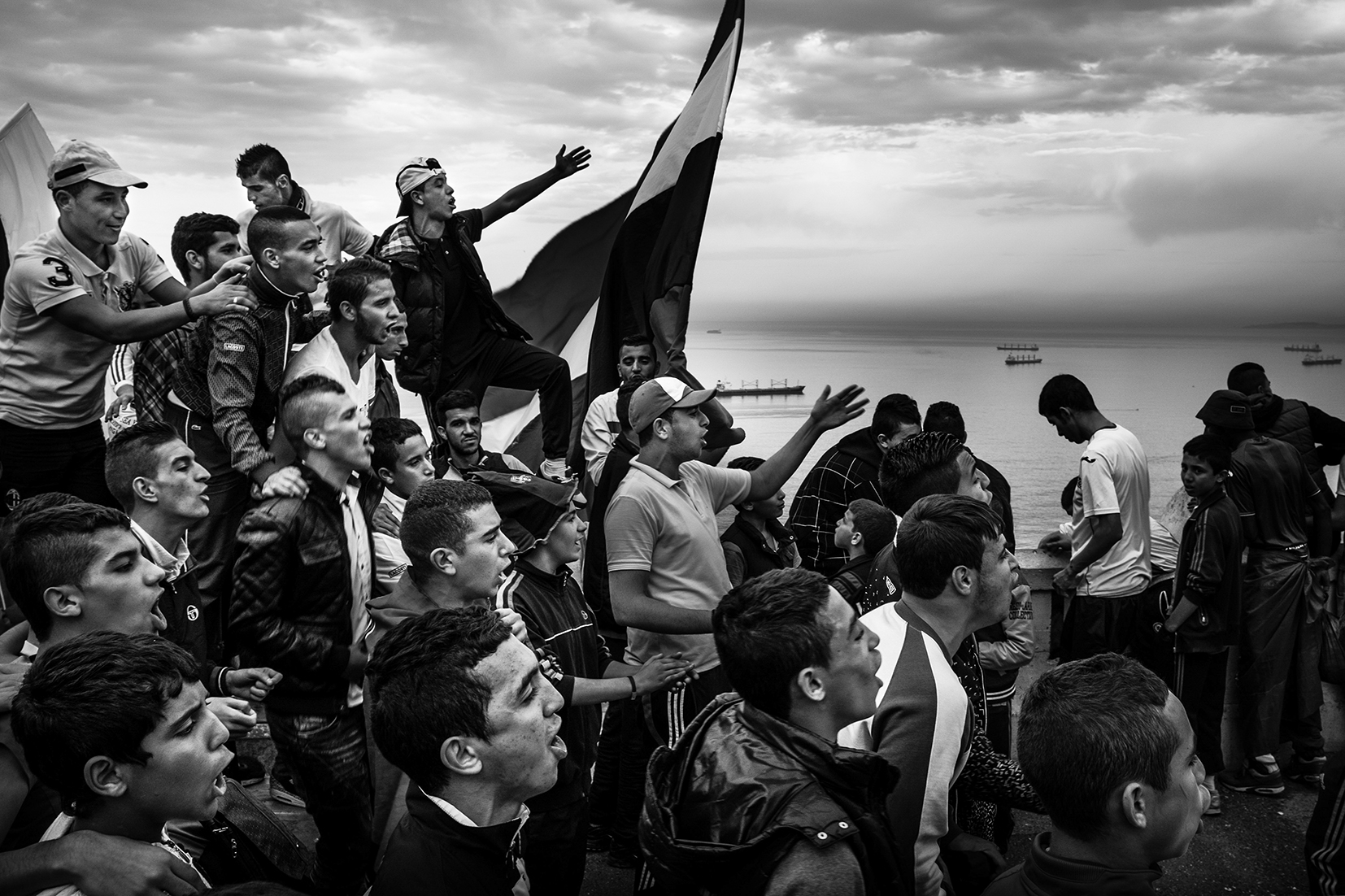 Black and white photograph of a crowd of young men standing above a bay, all looking shouting in a single direction. One holds a flag.