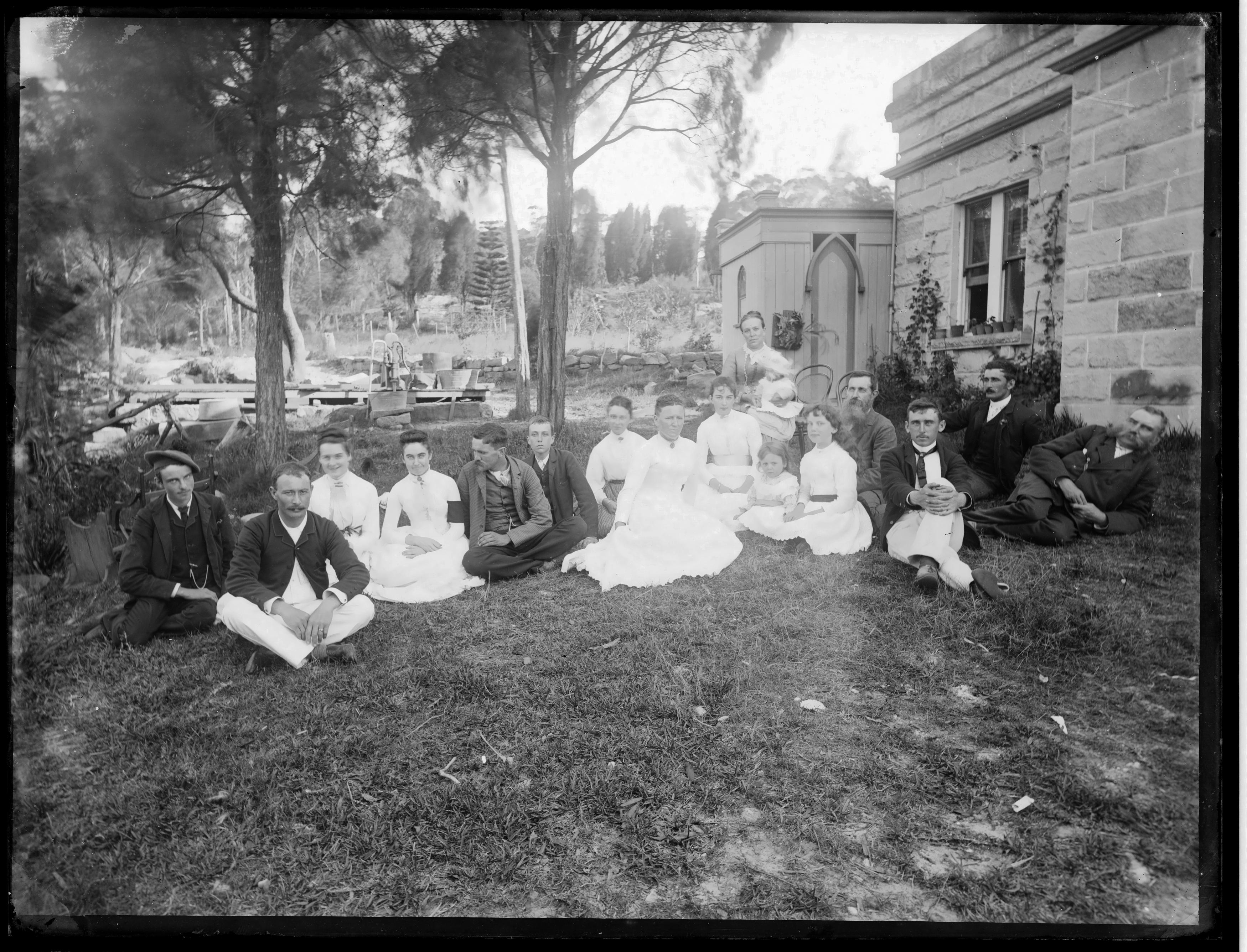 Black and white photograph of family sitting on the grass next to a sandstone homestead.