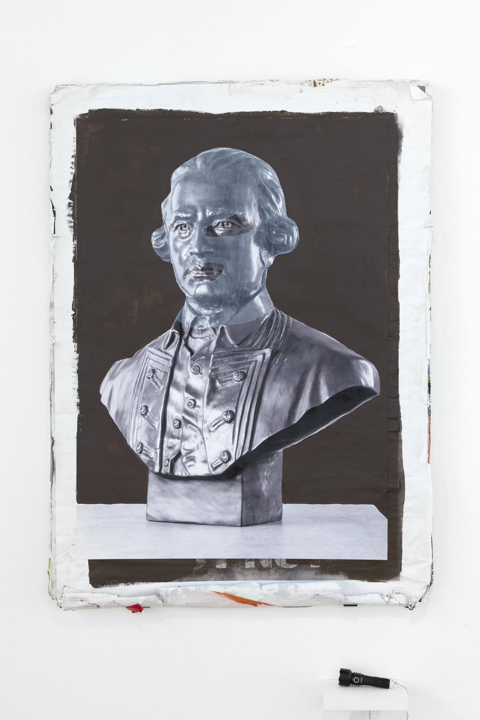 Painting of a bust, hung on a wall, with supplied black light torch nearby.