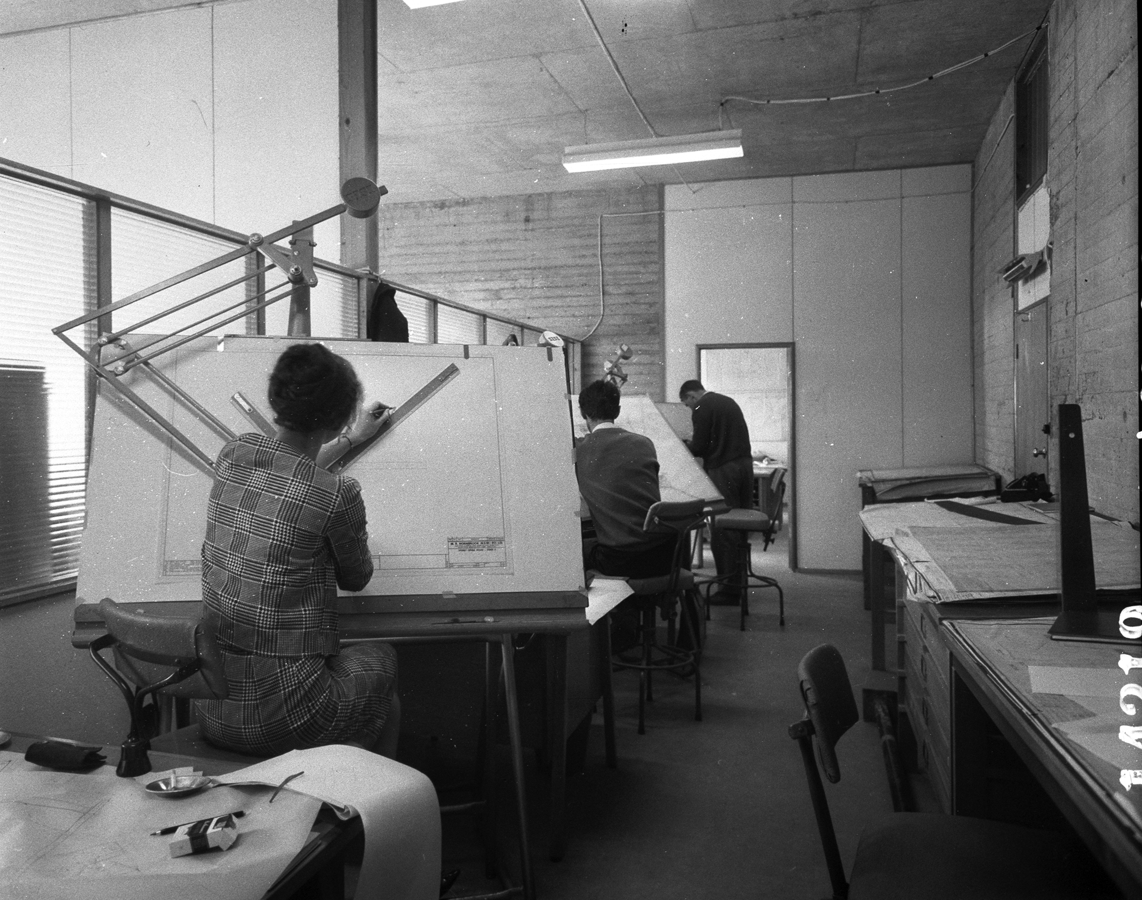 A black and white photograph of architects working at drafting tables in 1963
