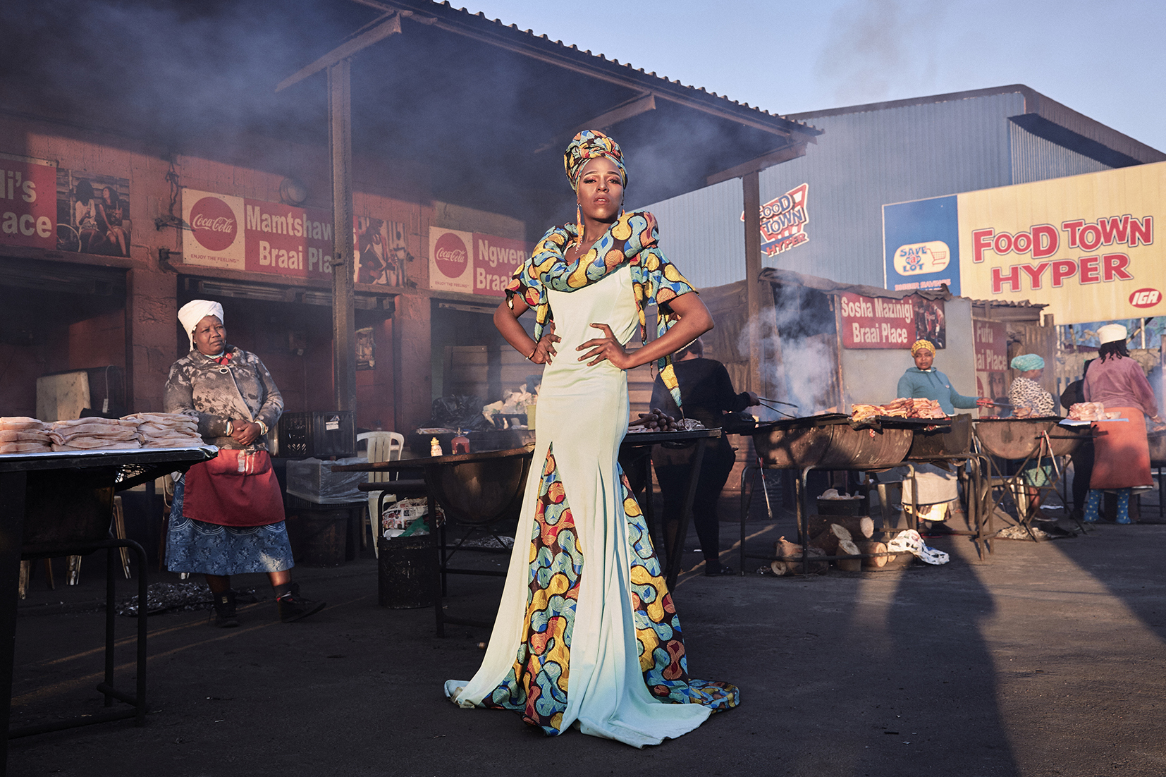 Photograph of  man standing in front of BBQ food vendors in an African market - he stands tall gazing at the camera with hands on hips wearing a long colourful dress, head scarf and makeup.