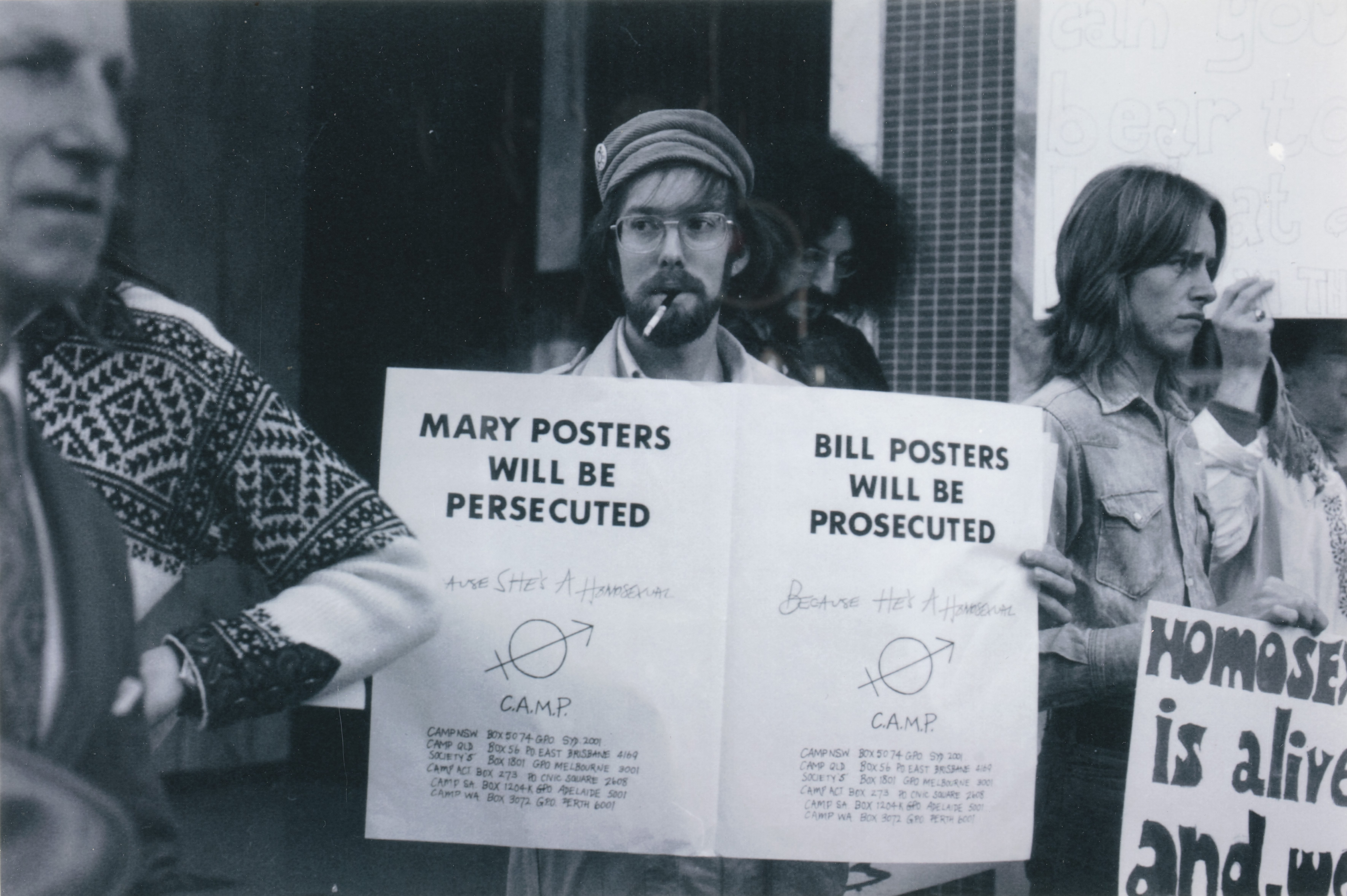 Lex Watson holding double poster: 'Mary Posters will be Persecuted/ Bill Posters will be Prosecuted', CAMP/Sydney Gay Lib demonstrators outside ABC Headquarters, Castlereagh Street, Sydney.