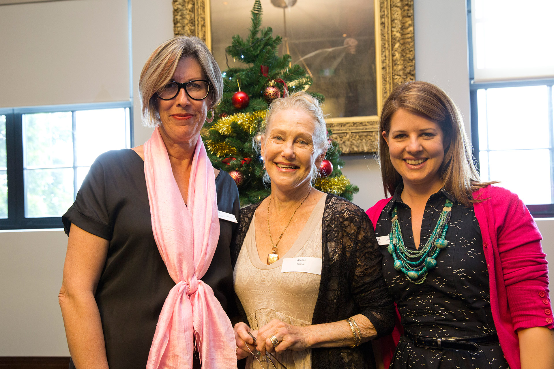 Three women with Christmas tree behind them