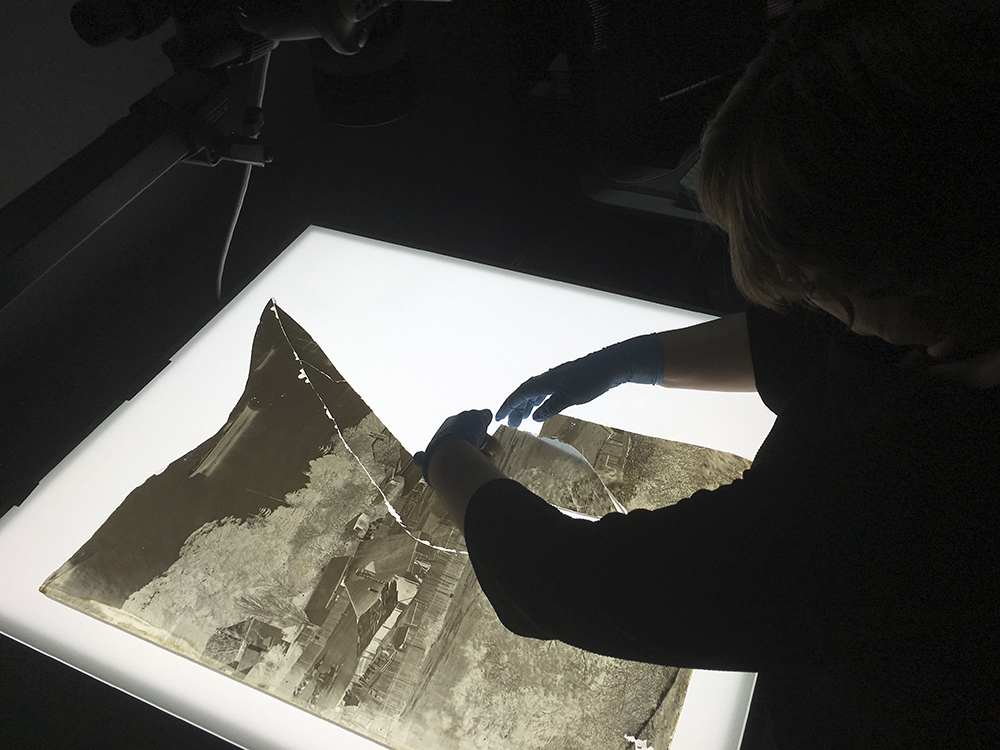 Person from the Library's Collection Care reassembling a section of the shattered Holtermann wet-plate glass negative for digitisation.