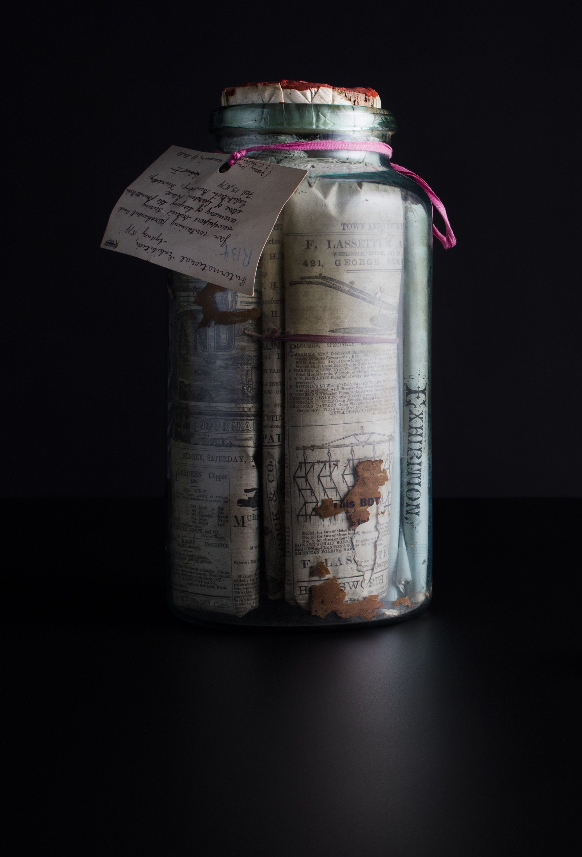 Glass jar filled with parchment and newspapers with cork stopper and red wax seal