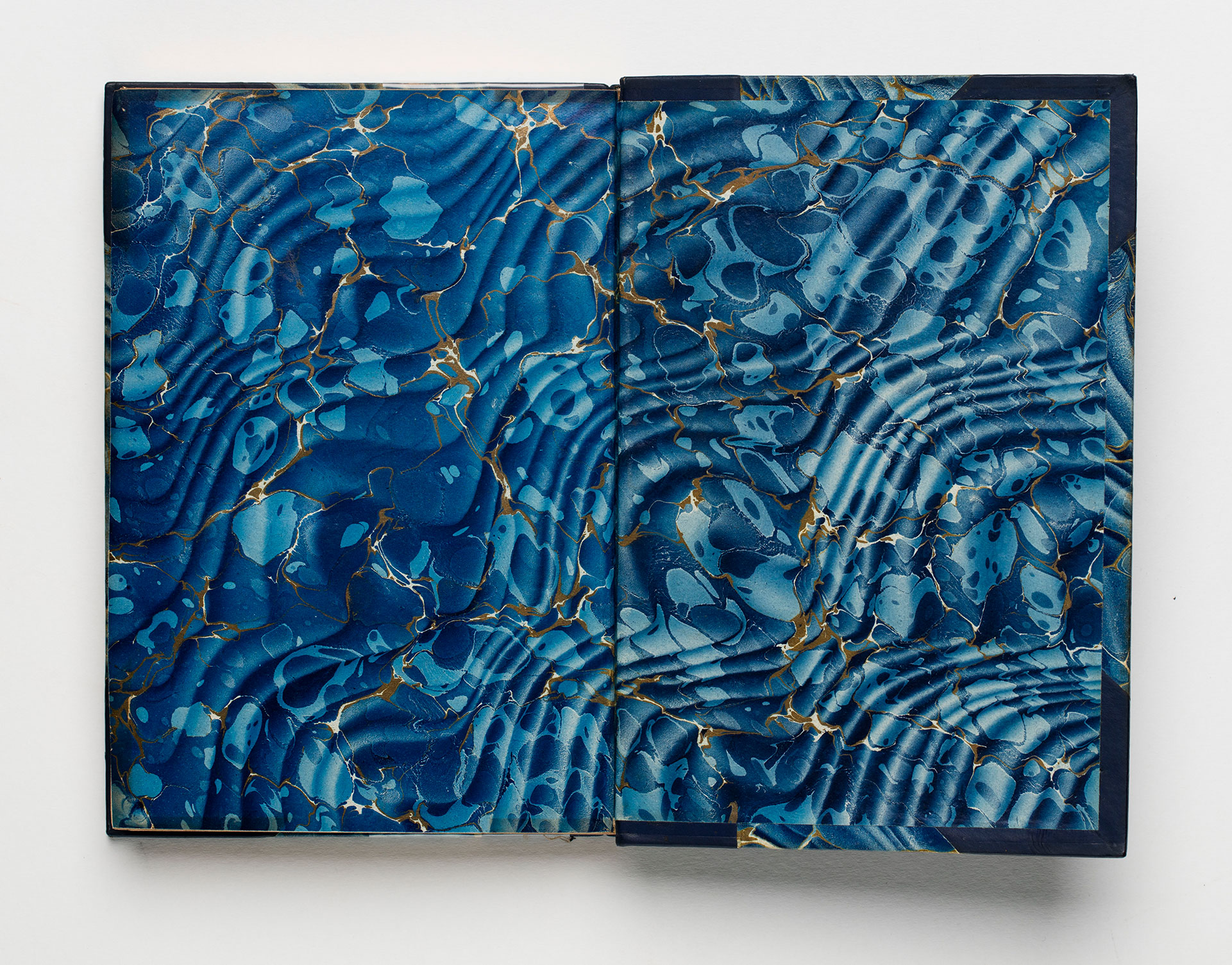 An endpaper patterned in ripples of blue and gold.