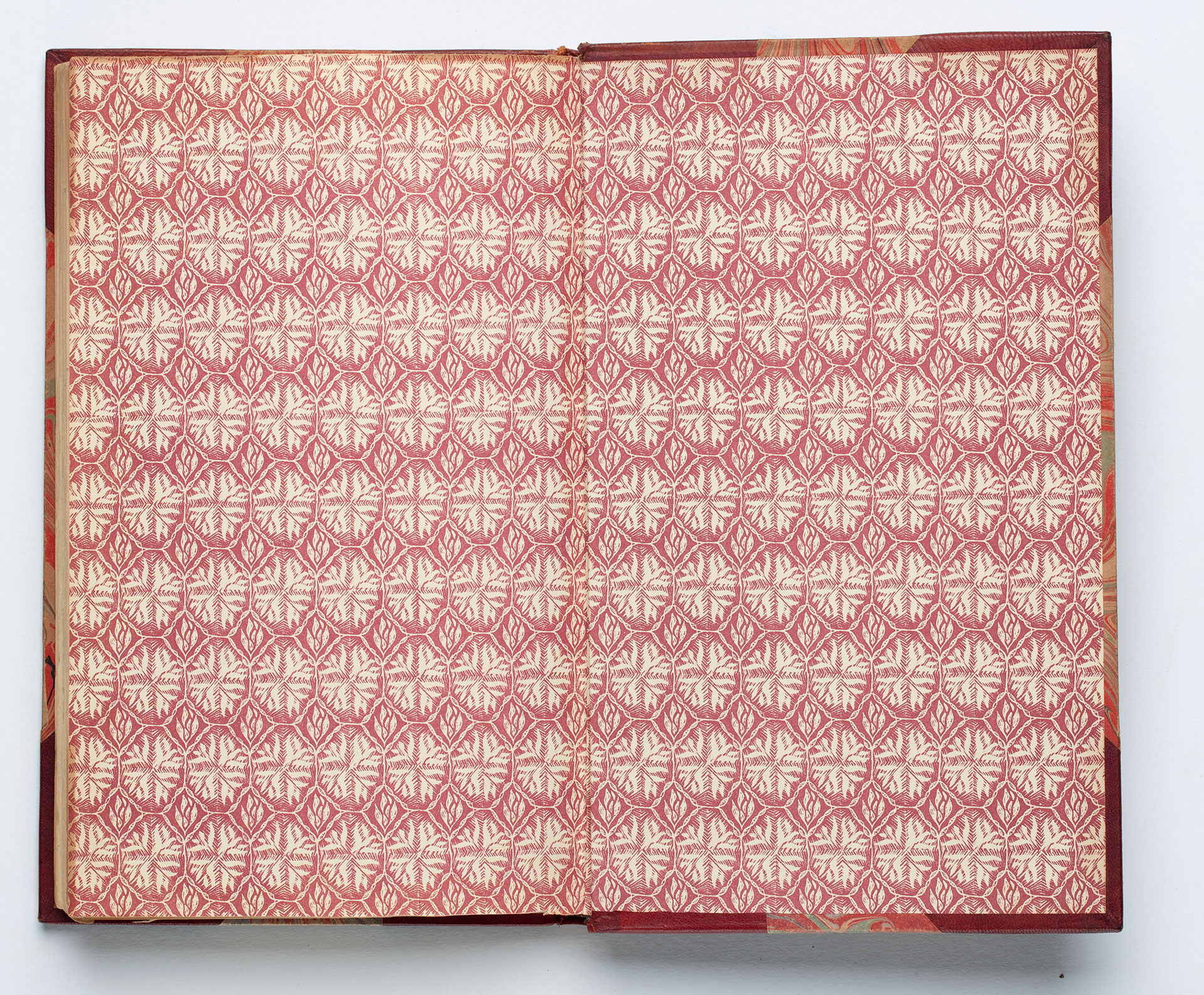 Endpapers with a repeating red floral pattern.