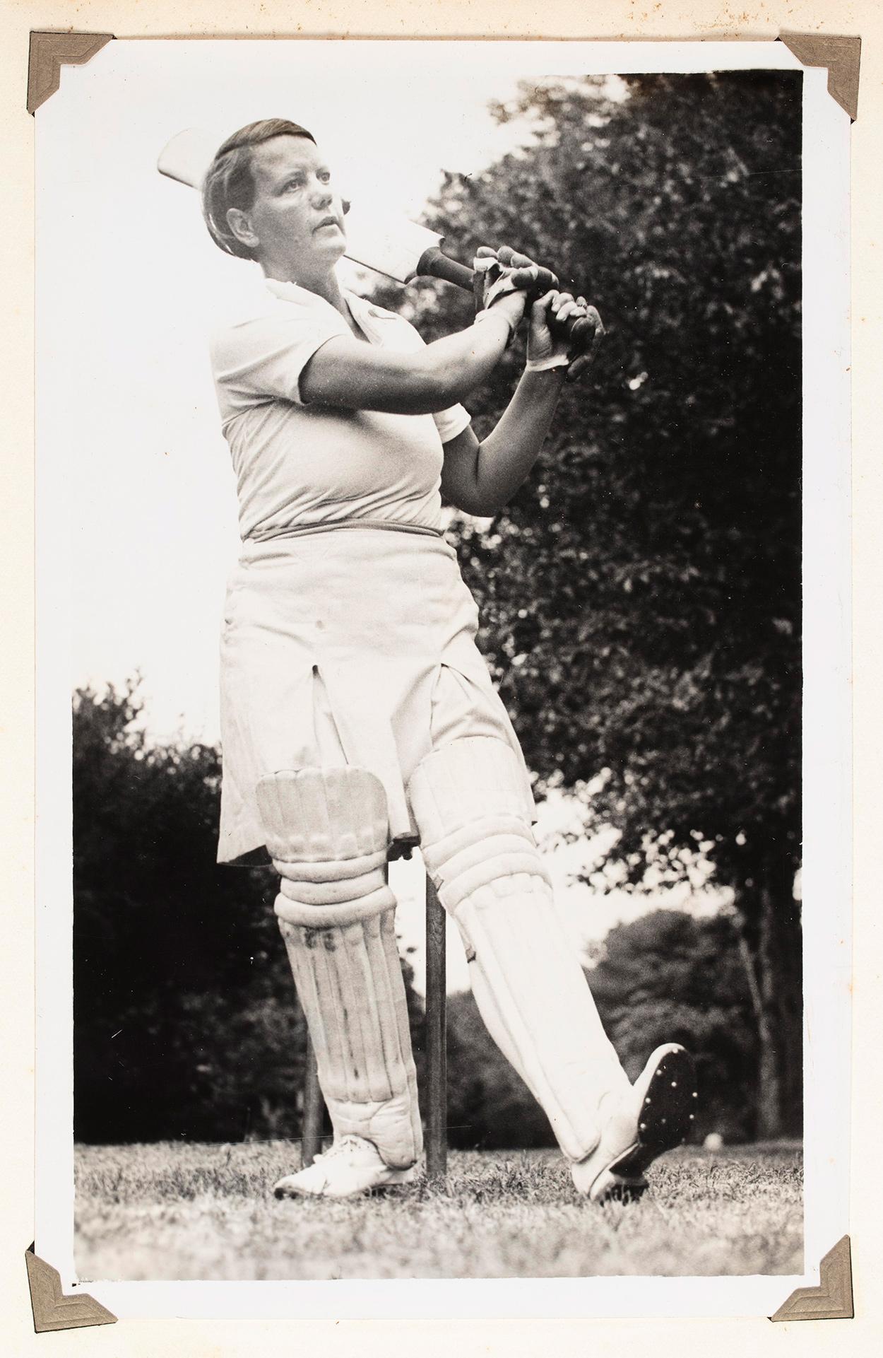 A woman in cricket uniform, swinging a cricket bat.