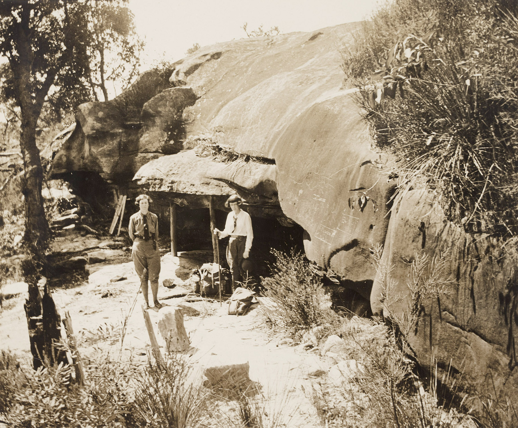 two women stand outside a cave in a rock face