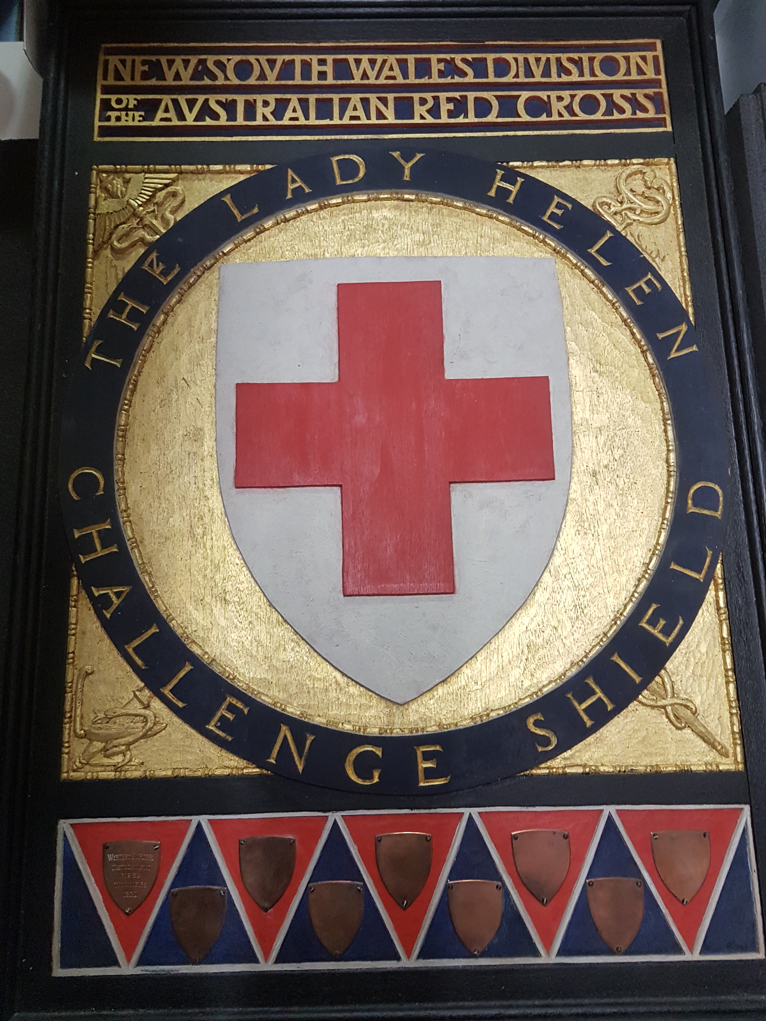 This beautiful woodcut shield, hand painted in gold and black with a red cross in the centre and decorated with brass plates, was designed by Professor L. Wilkinson of the University of Sydney and executed by Eirene Mort and Nora Weston.