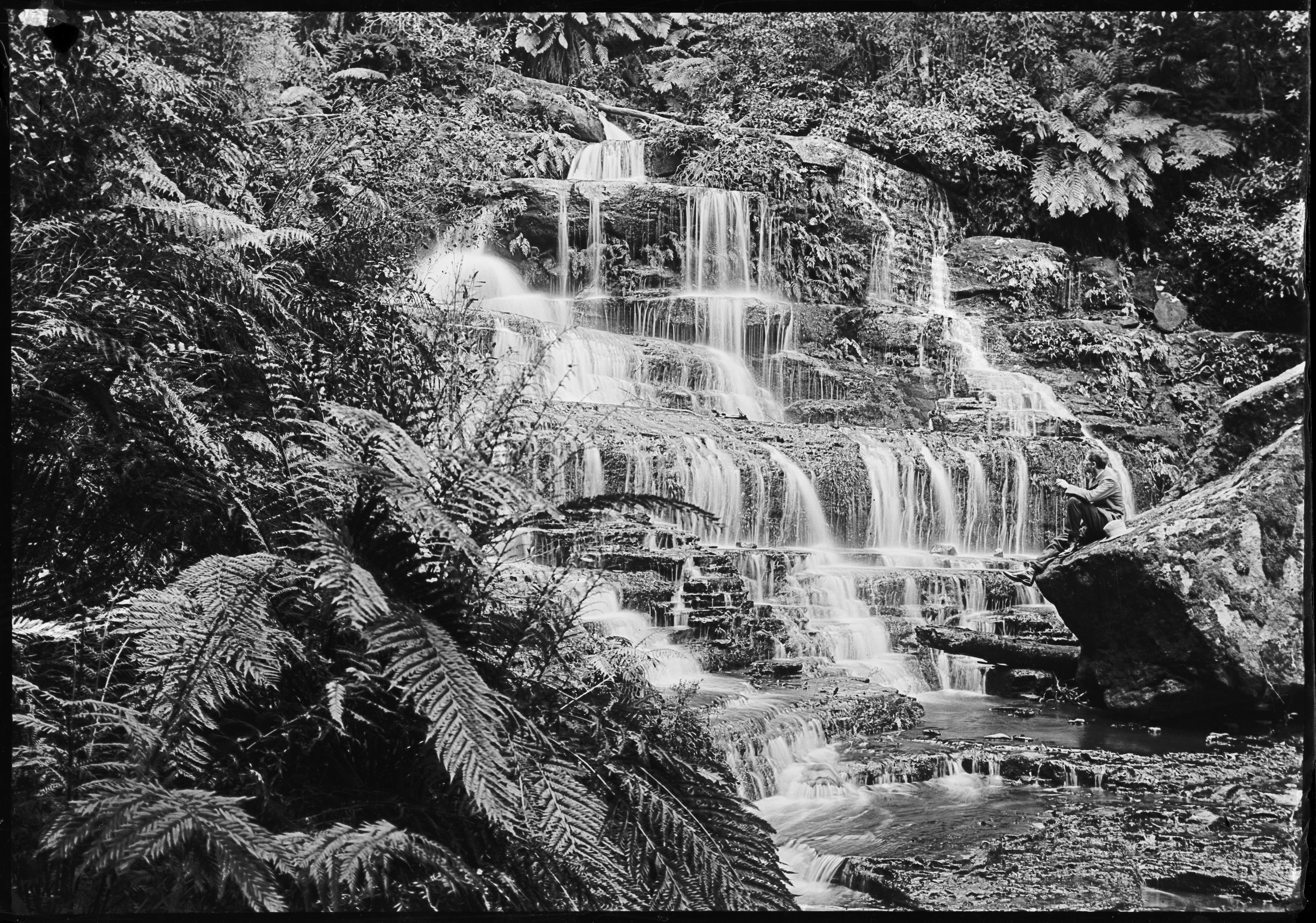 Black and white photograph of a cascading waterfall. A man sits on a rock in the foreground.