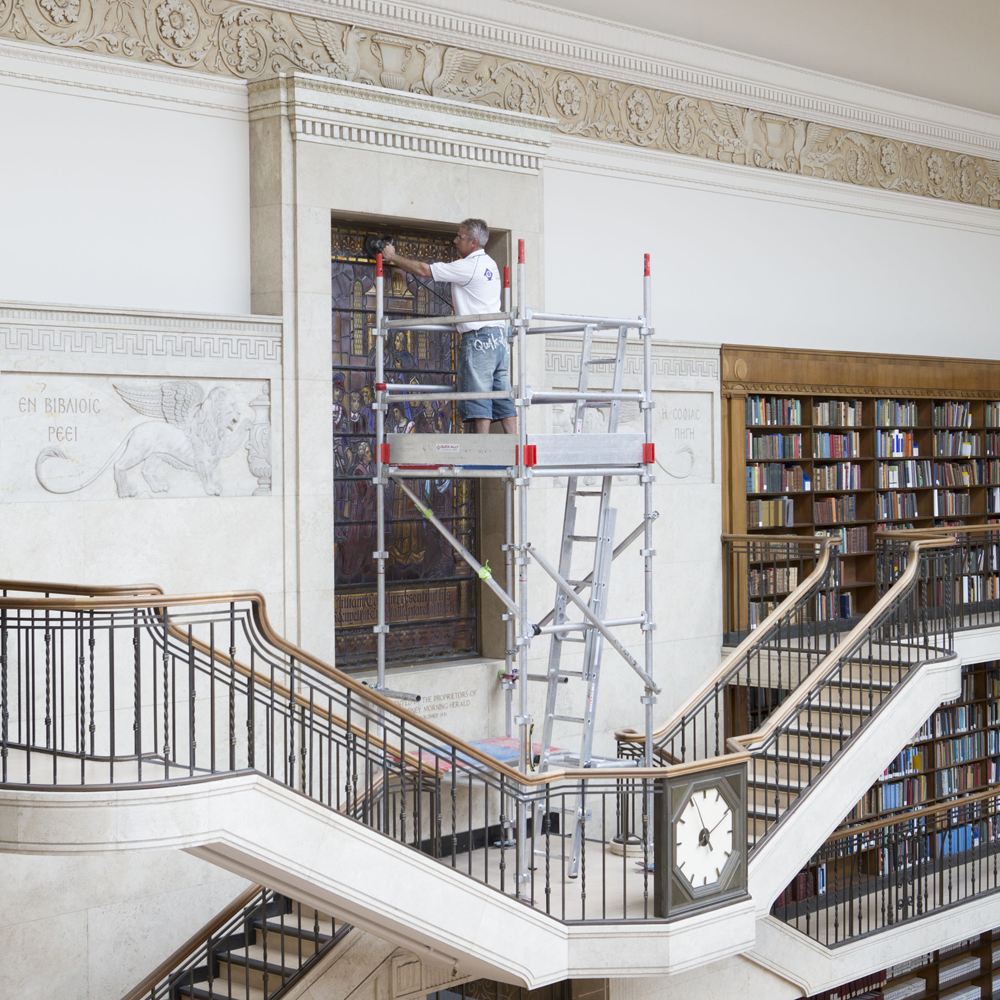 Workman on ladder in large room