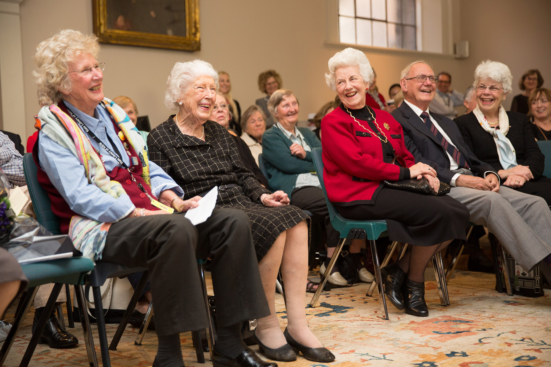 Several women sitting on chairs and smiling