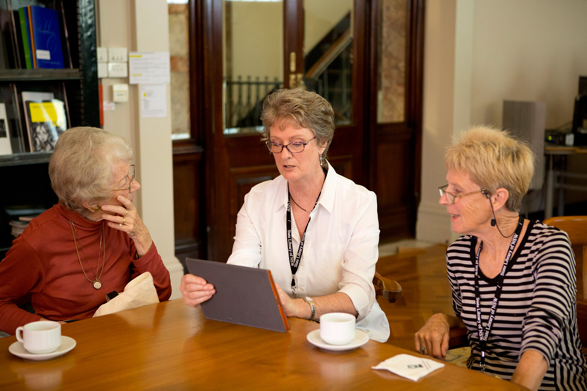 Three women sitting round a laptop at a desk in Friends Room