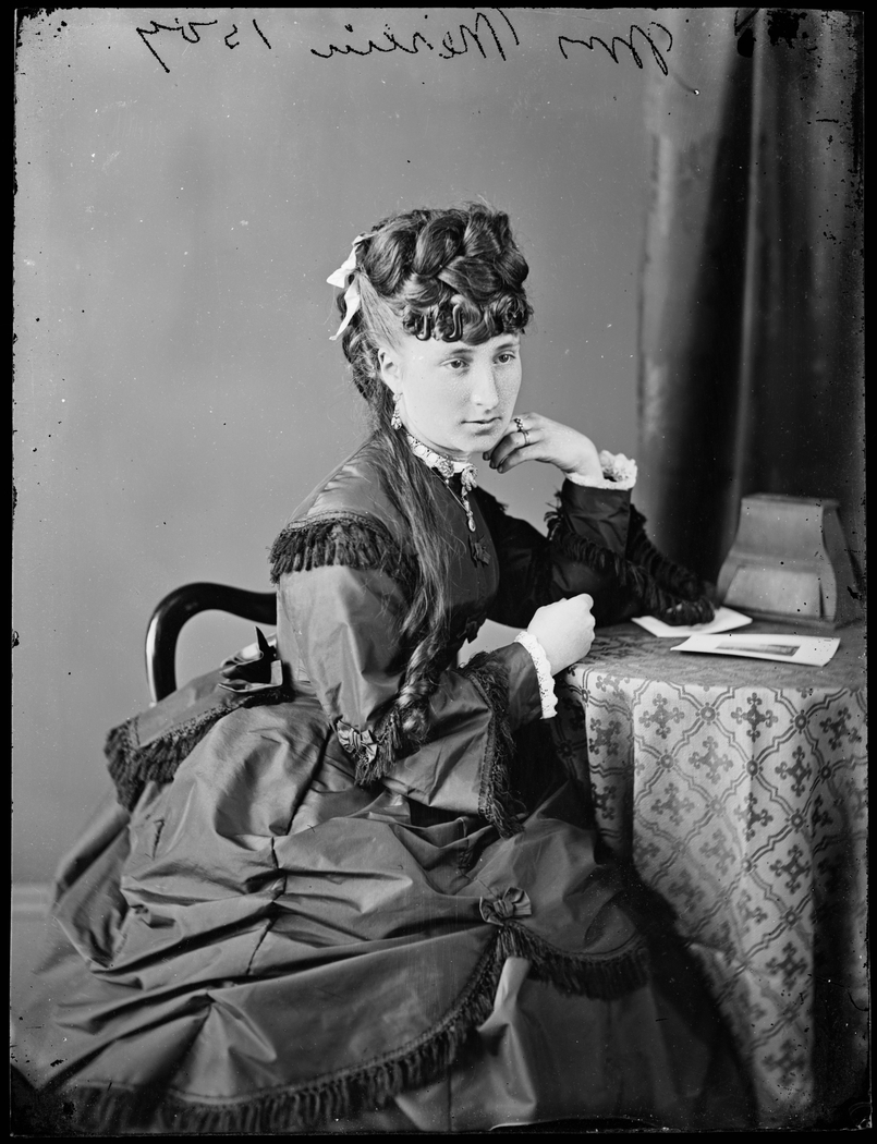 An old black and white photo of a woman with an elaborate hairstyle, in a contemplative pose sitting at a small round table.