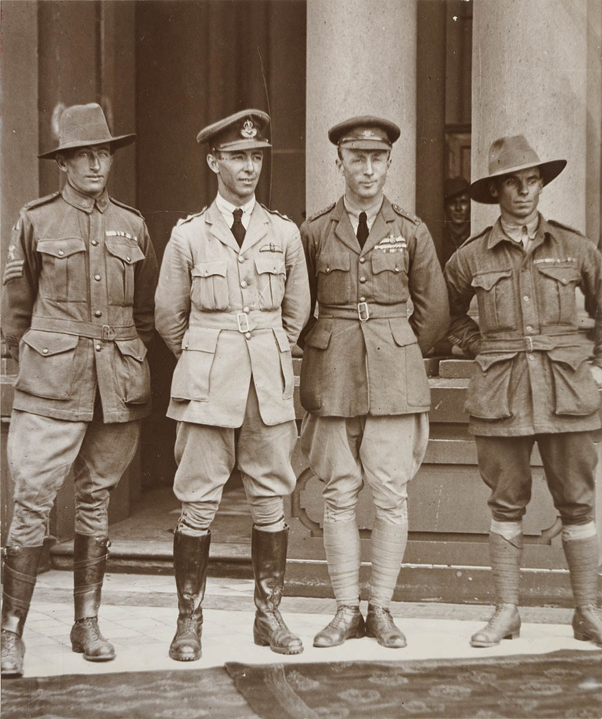 Black and white photograph of four soldiers standing in front of a sandstone building posing for the camera.
