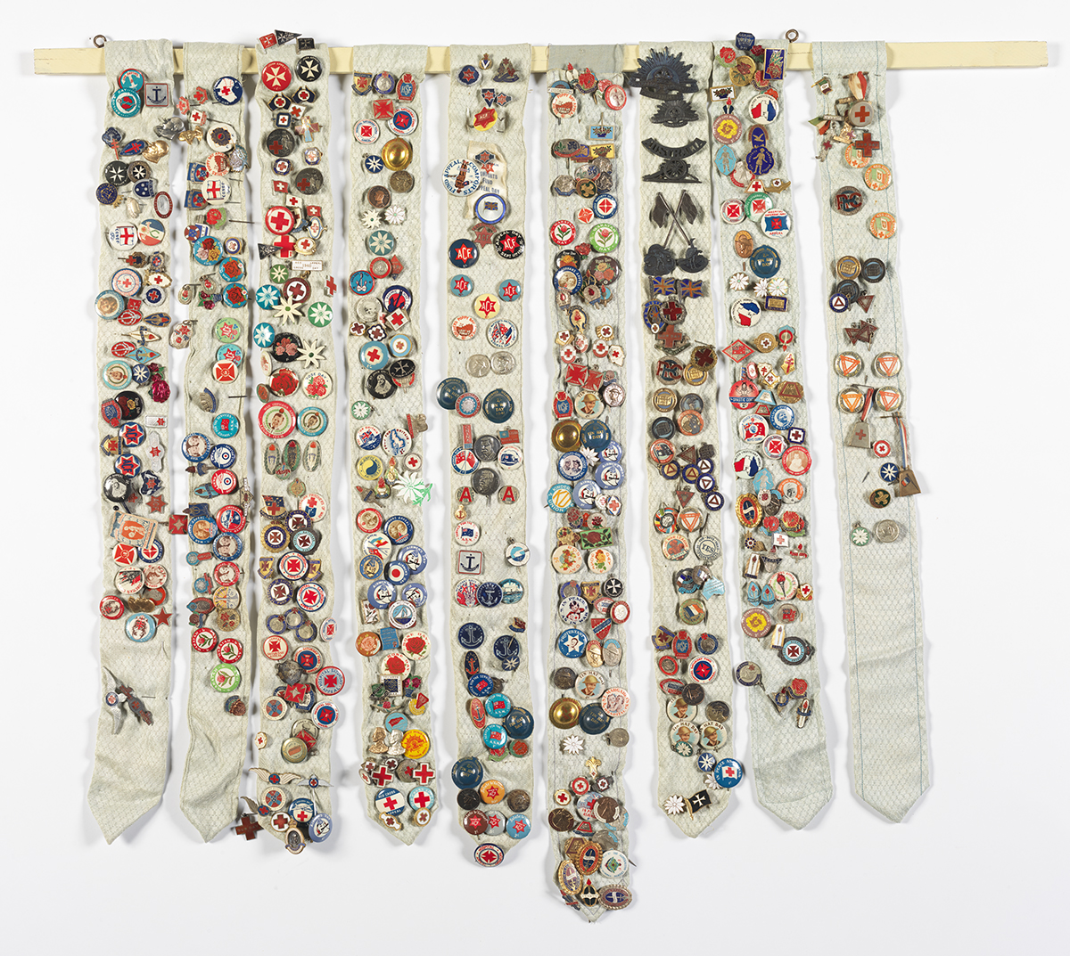 Photograph of 9 long strips of fabric holding hundreds of colourful badges.