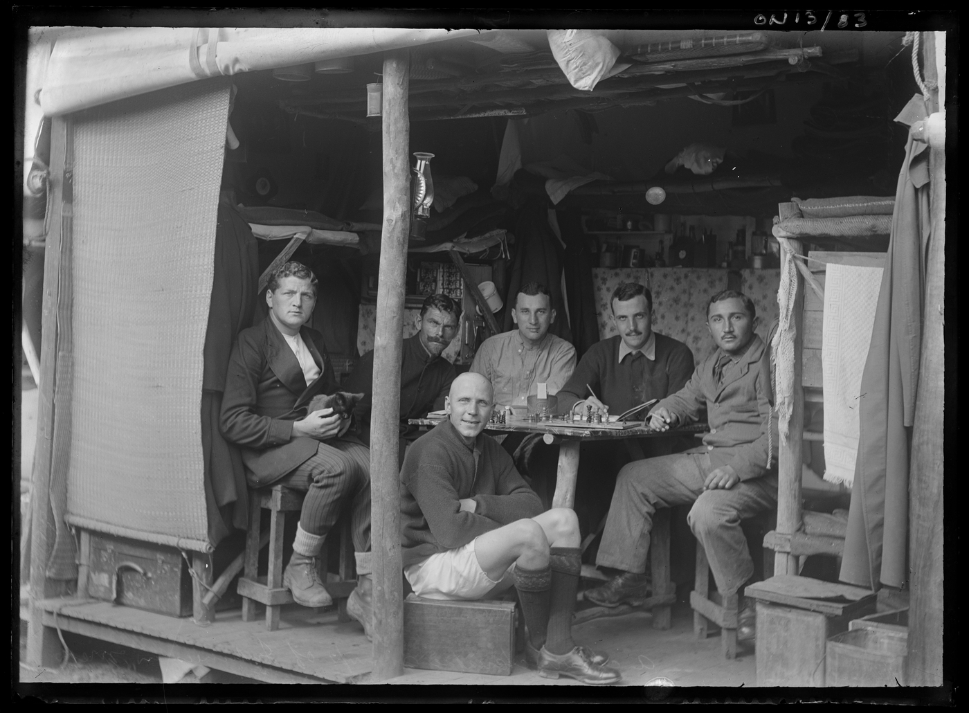 Black and white photograph of men sitting around a table playing chess, in a make shift shelter.