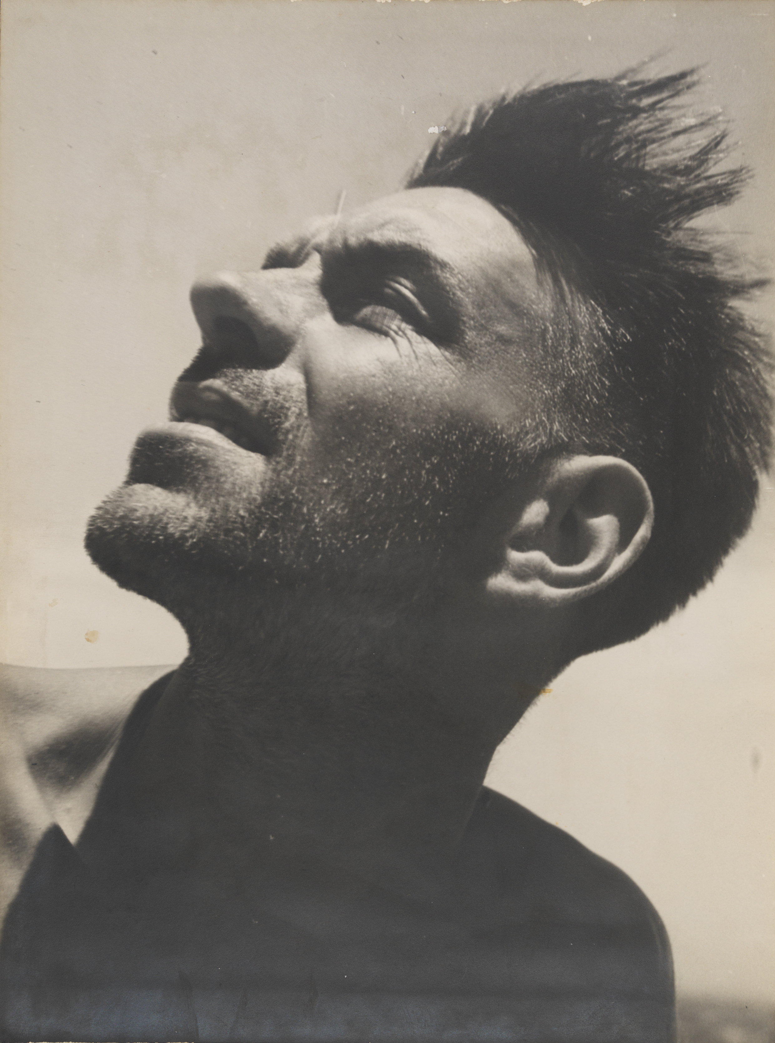 A sepia photographic portrait of a man tilting his face up to the sun.