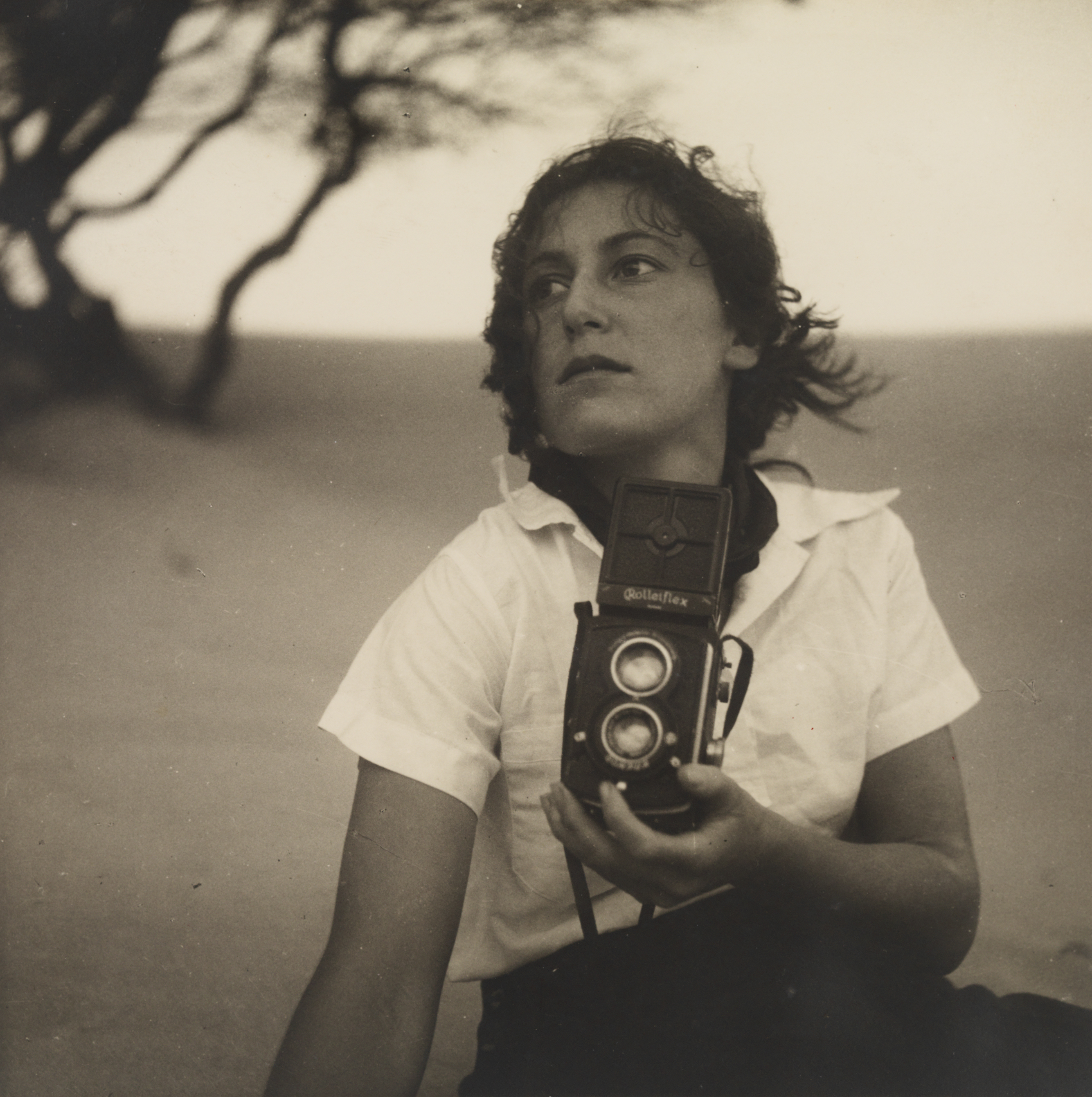 A sepia photographic portrait of a woman sitting on a beach gazing off to the size, holding an old camera up in front of her