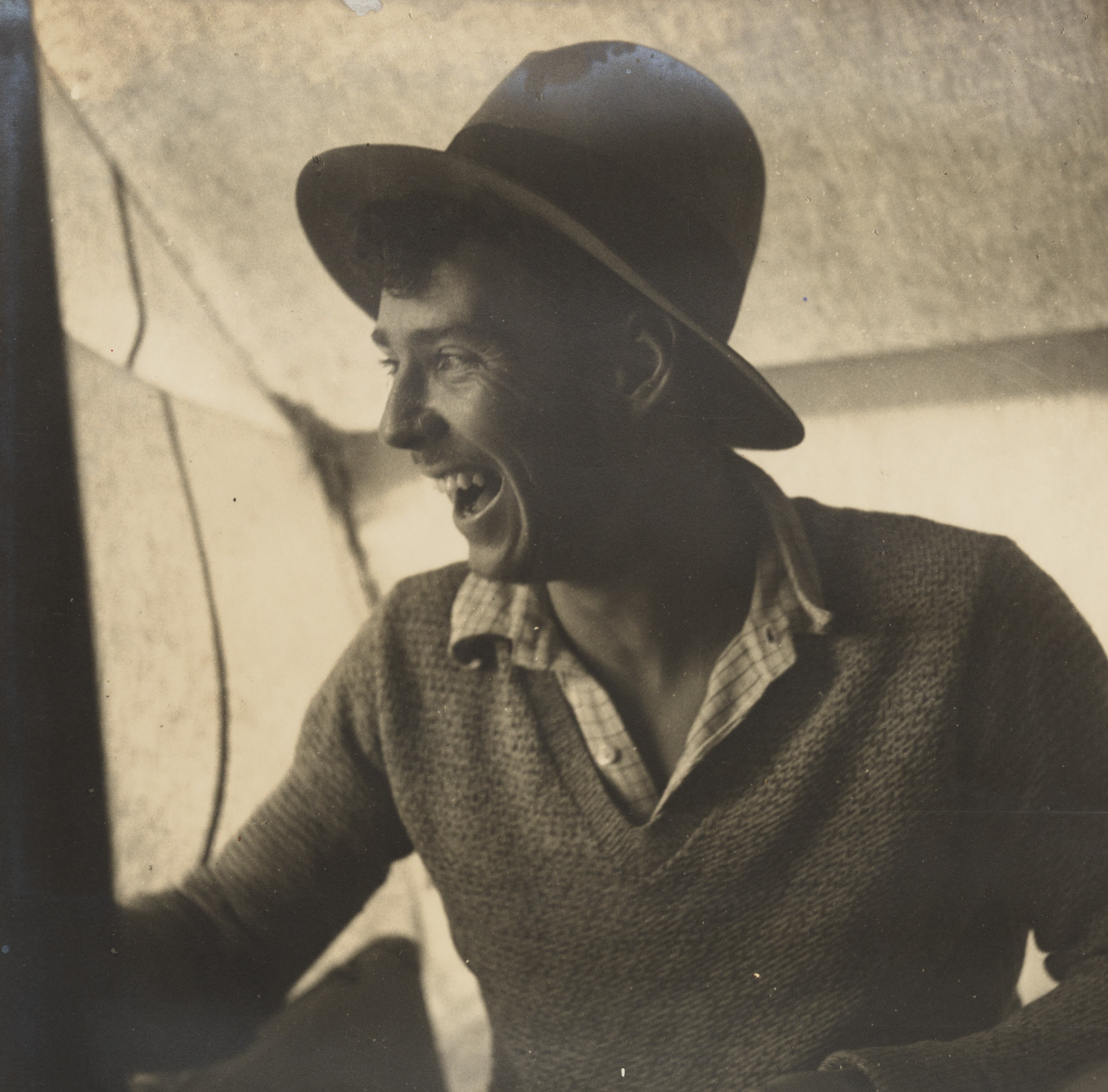 A sepia photograph of a man wearing a hat, checked shirt and wollen jumper sitting inside a canvas structure, looking off to the side laughing.