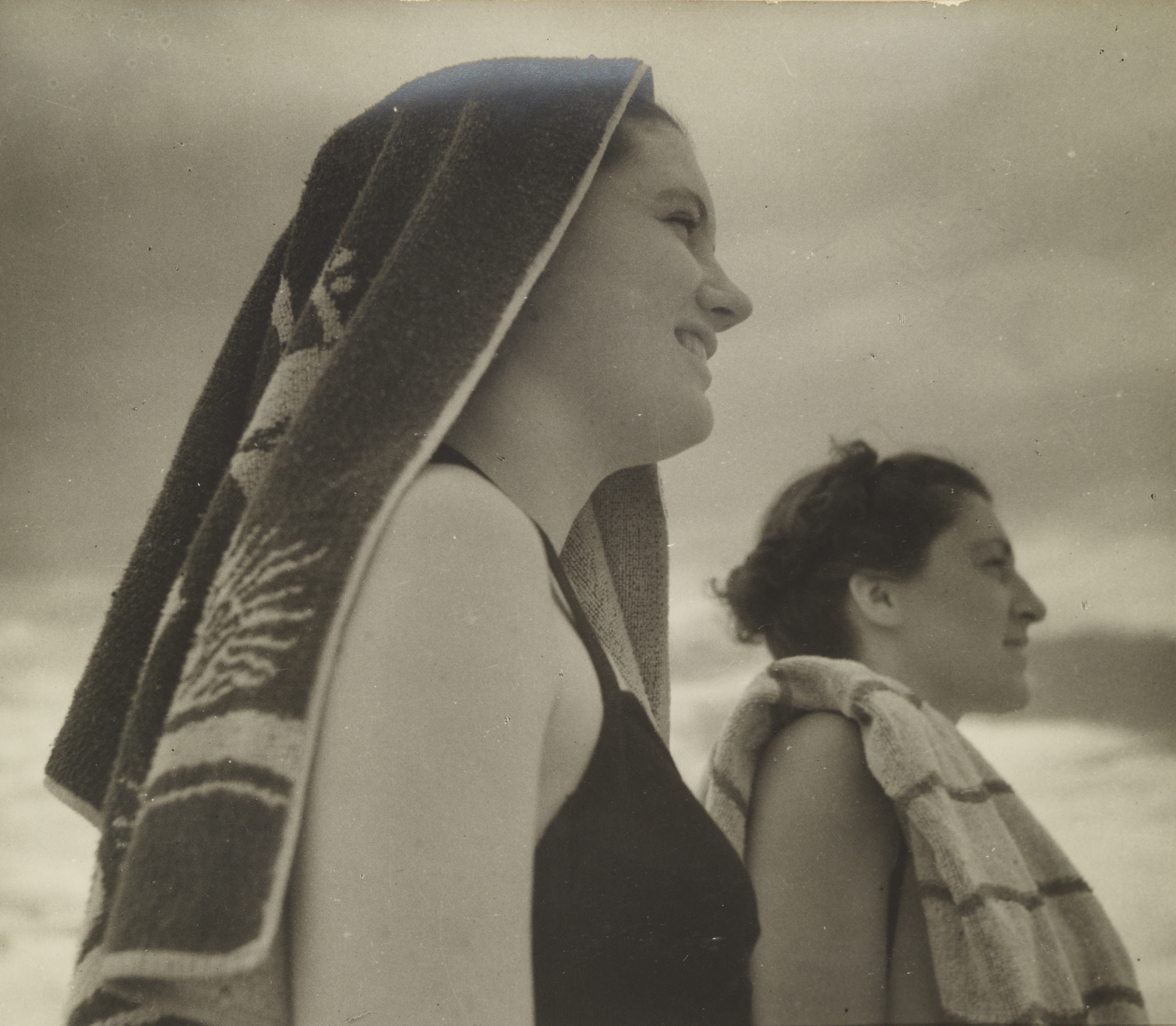 A sepia photograph of two women standing side by side in profile. The woman in the foreground has beach towel draped over her head.