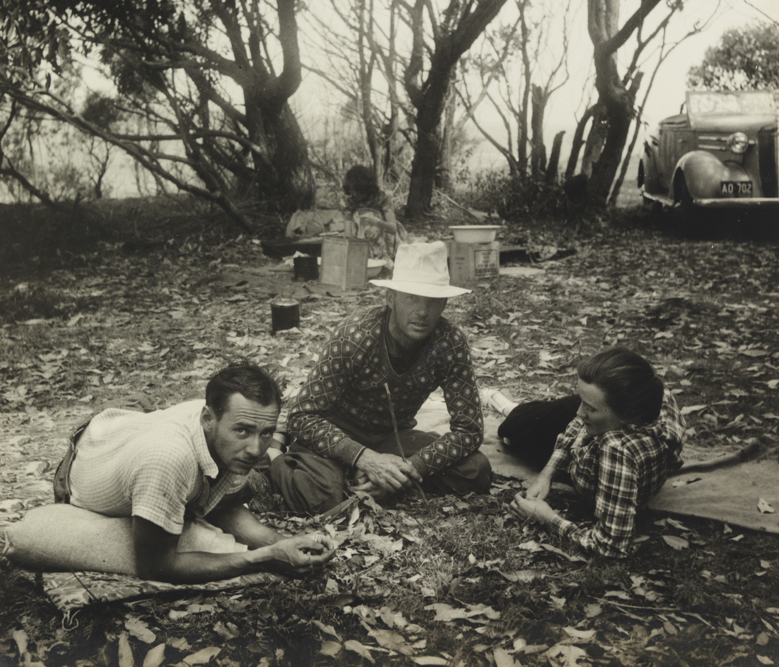 A black and white photograph of two men and a woman sitting on a leaf littered ground. In the background a 1930s style car is parked and woman prepares food in a makeshift camp kitchen.
