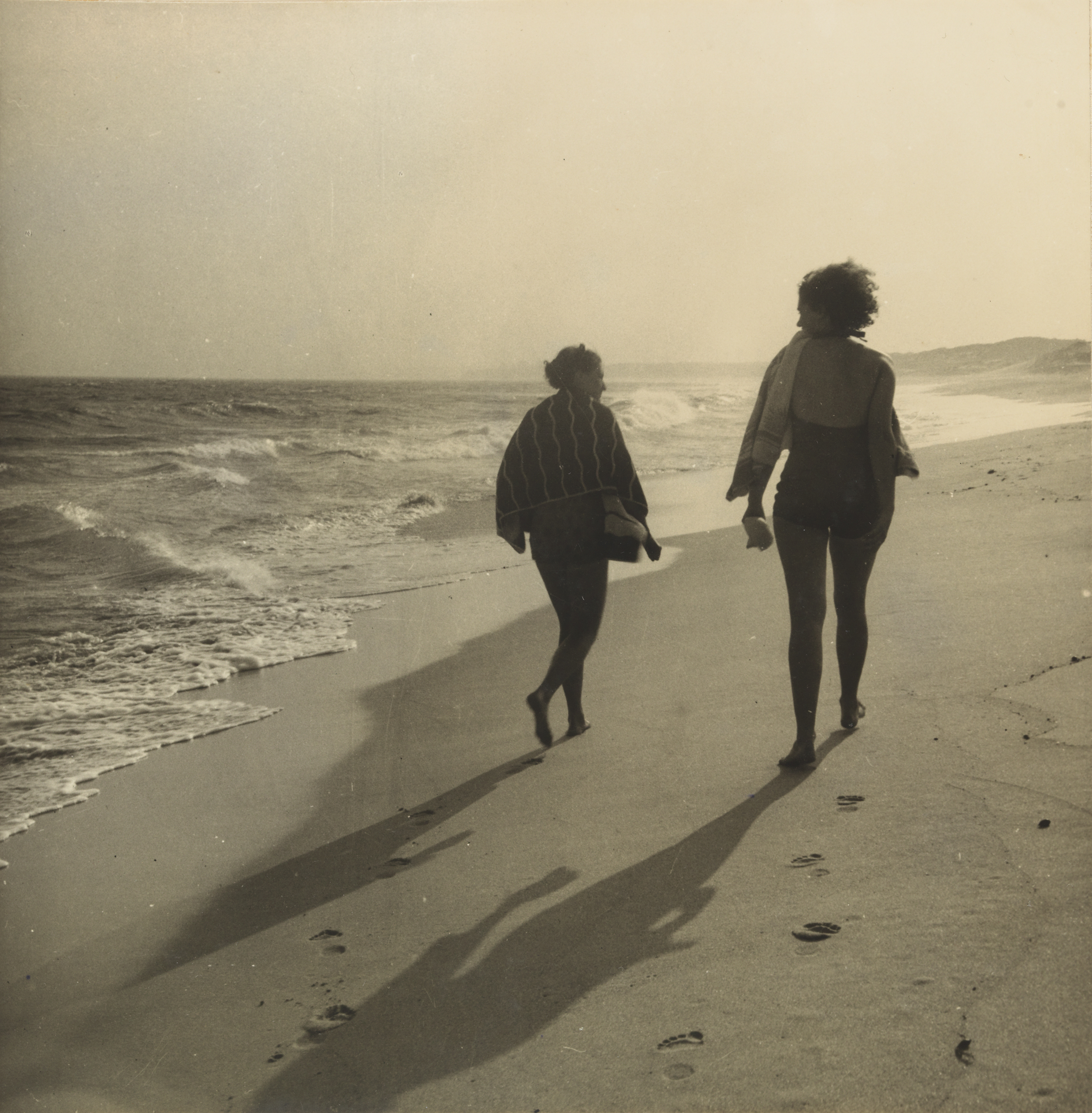 A sepia photograph of two women walking along the shoreline of a beach.