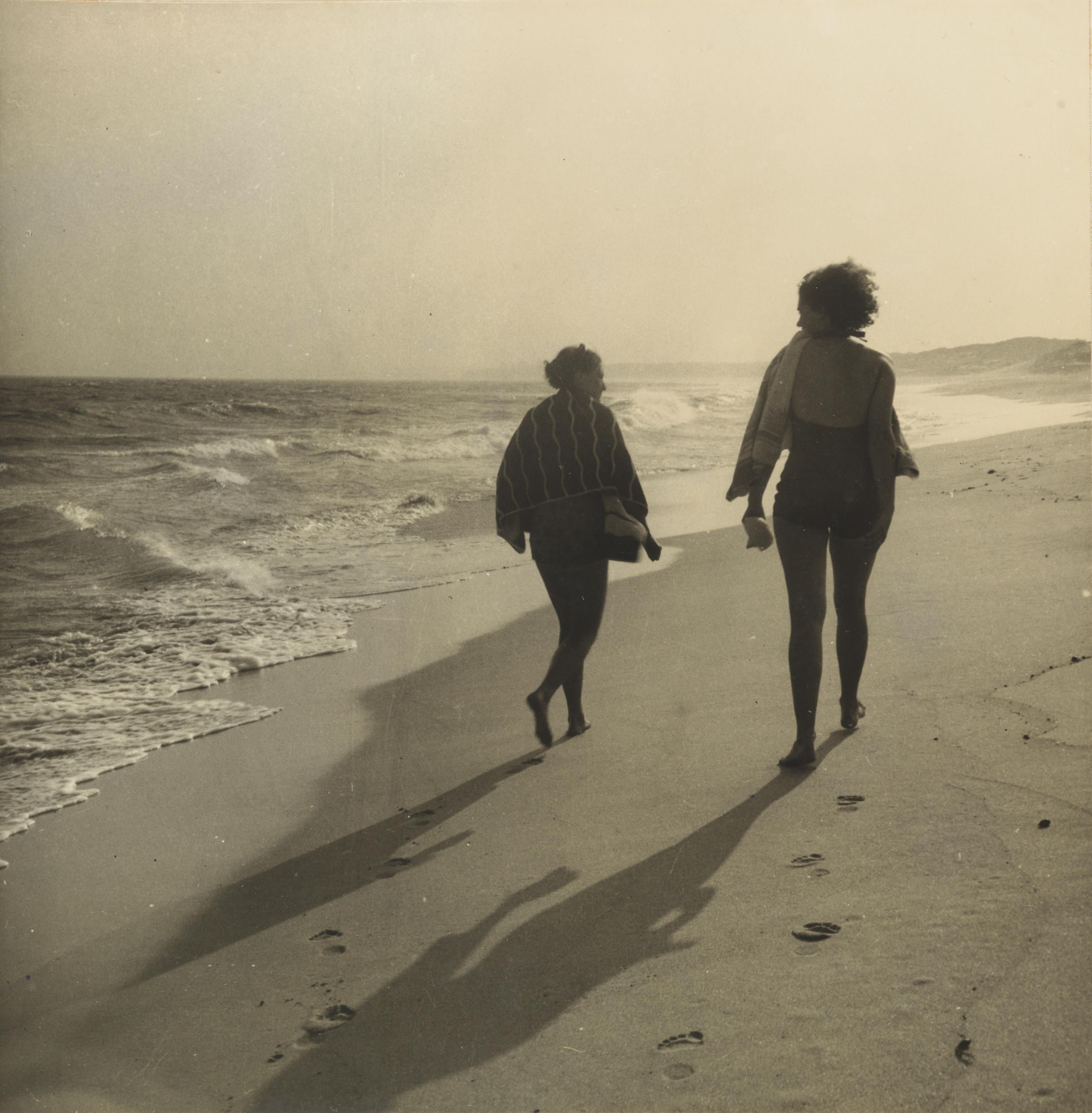 A sepia photograph of two women walking along the shoreline of a beach.