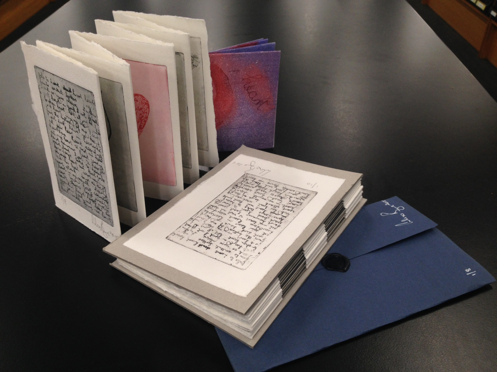 Four artists' books shown together on a table