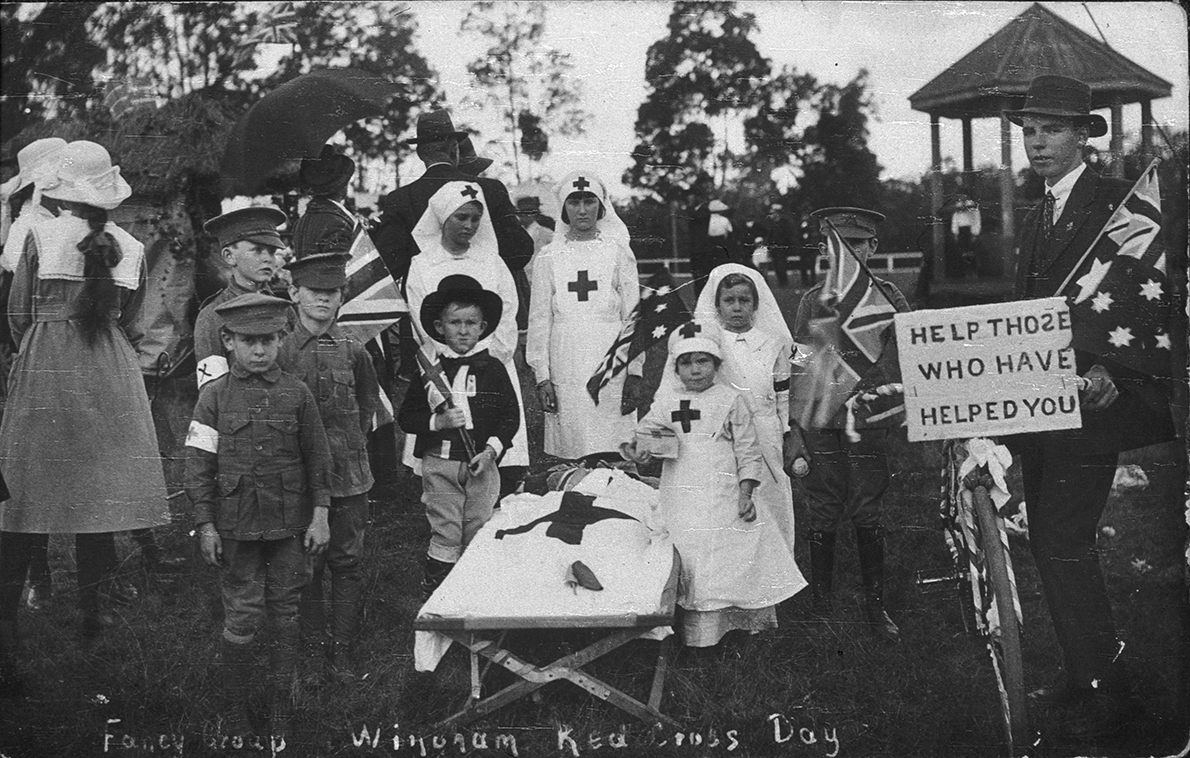 Black and white photograph of children dressed up in nurses and medics posing for the camera. A mock stretcher stands in the middle of the group.