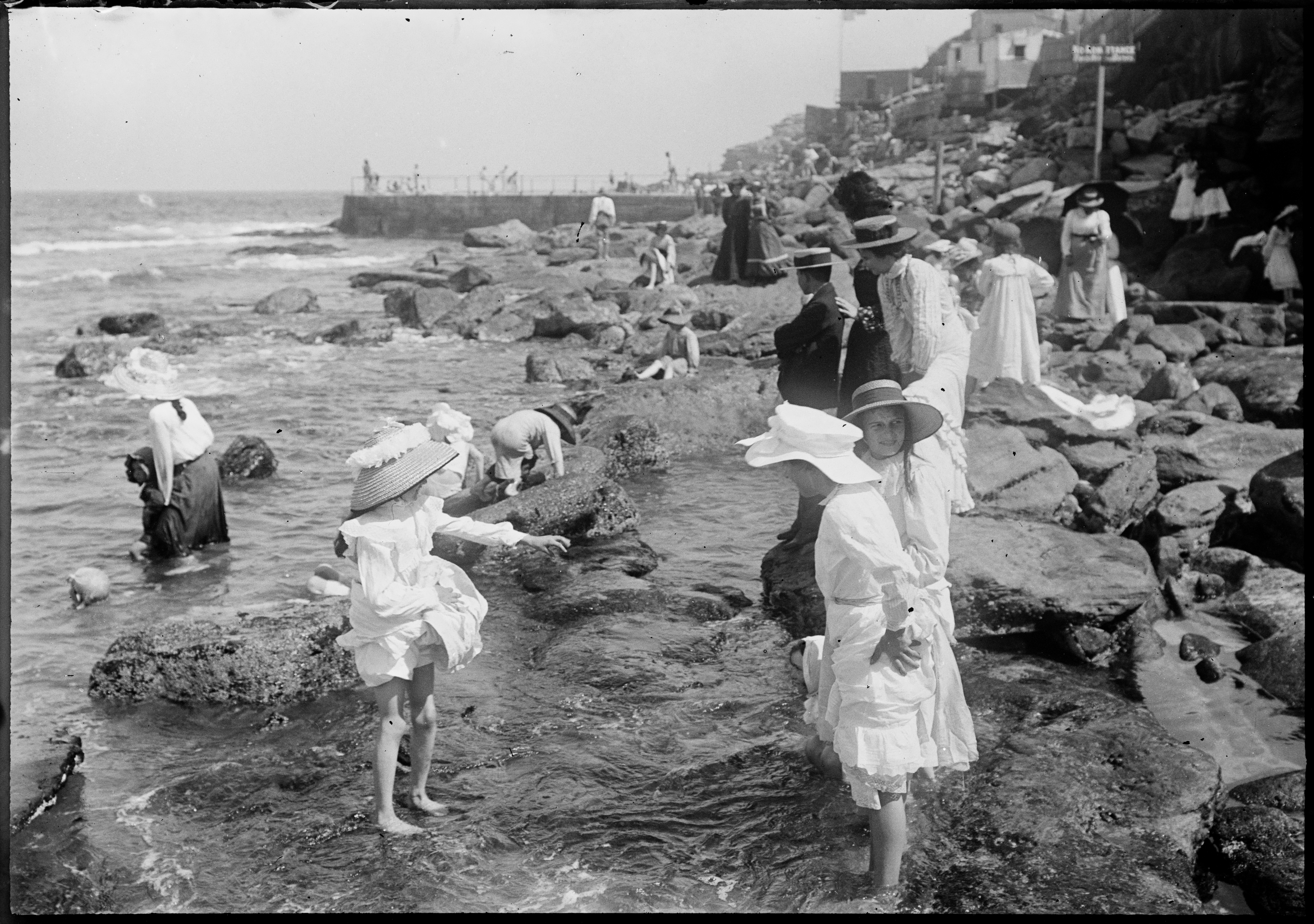 Children paddling in rock pools with swimming baths behind, South Bondi
