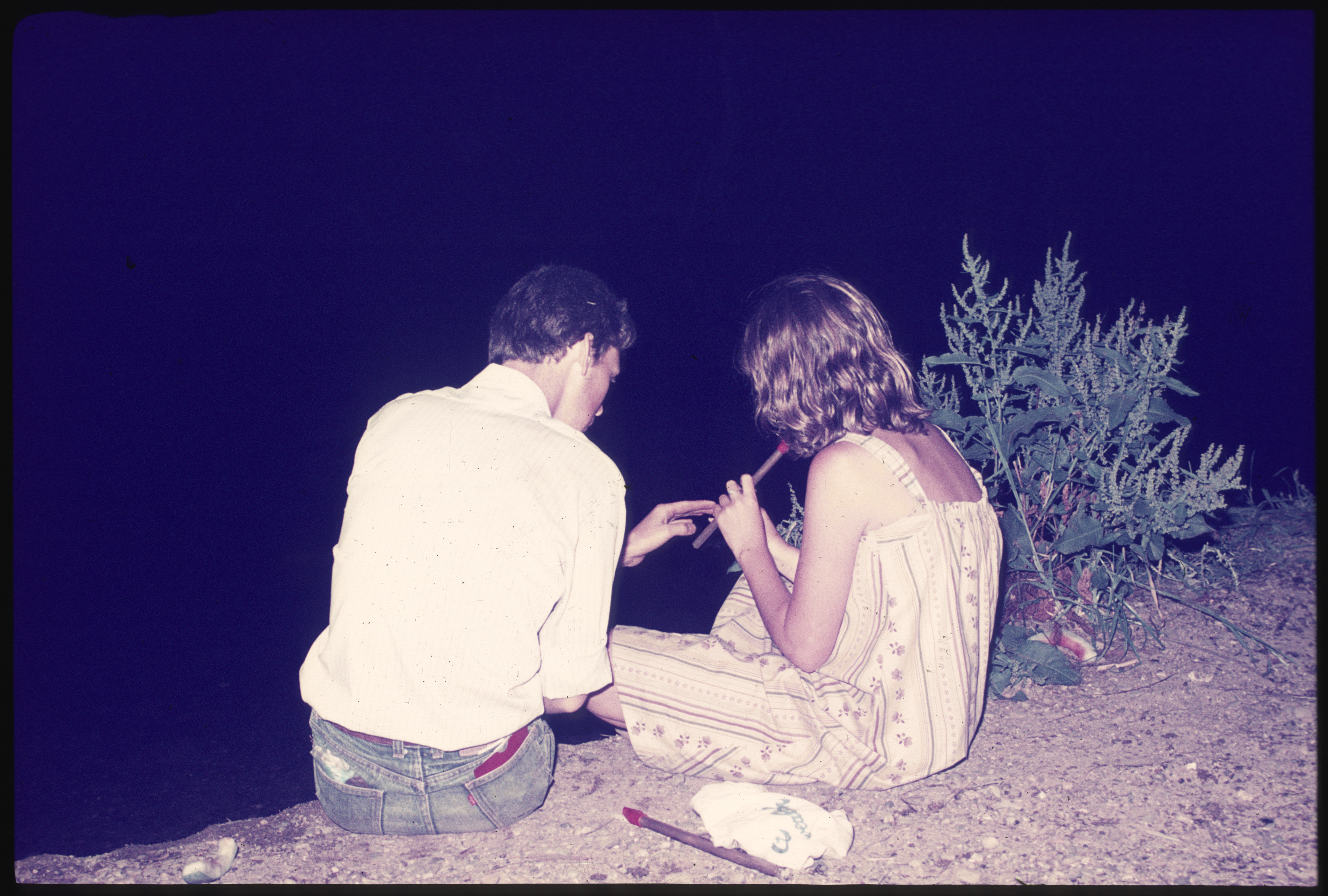 A man shows a woman how to play a pennywhistle while sitting on the bank of a river at night