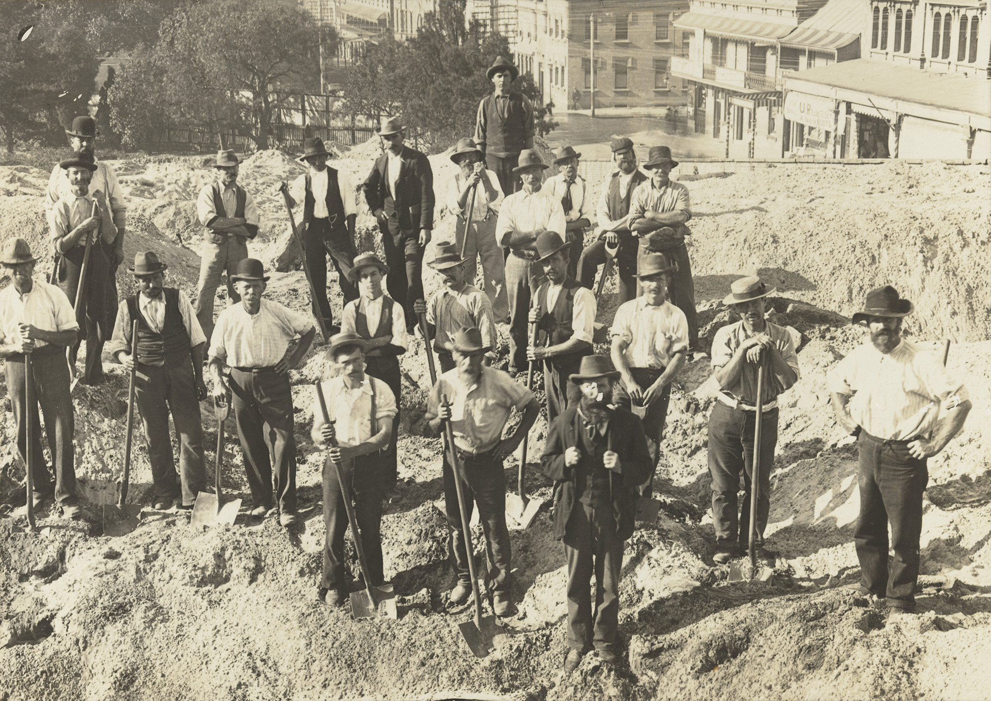 A sepia photograph of a group of workers, standing facing the camera, shovels in hand - they wear trousers, button up shirts and suspenders.