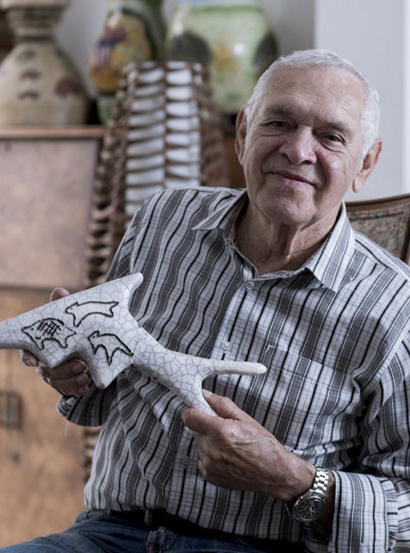 Portrait of a smiling man holding a ceramic fish.