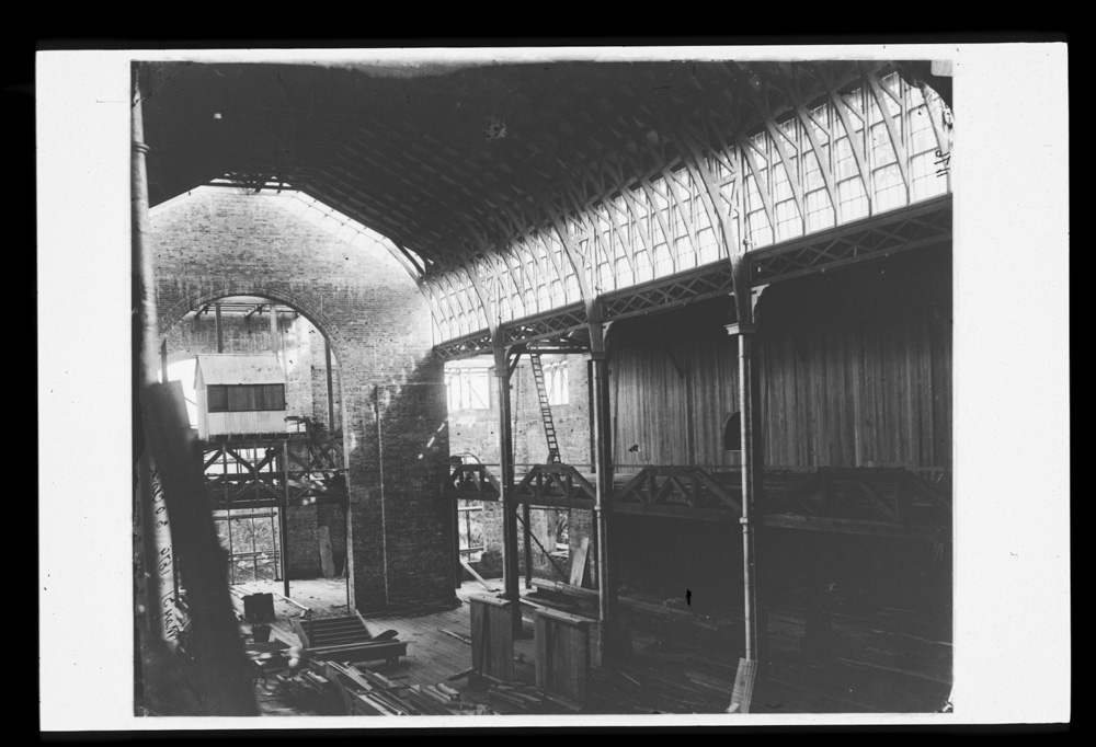 Interior of the Garden Palace Sydney during construction, showing high brick wall and wooden beams