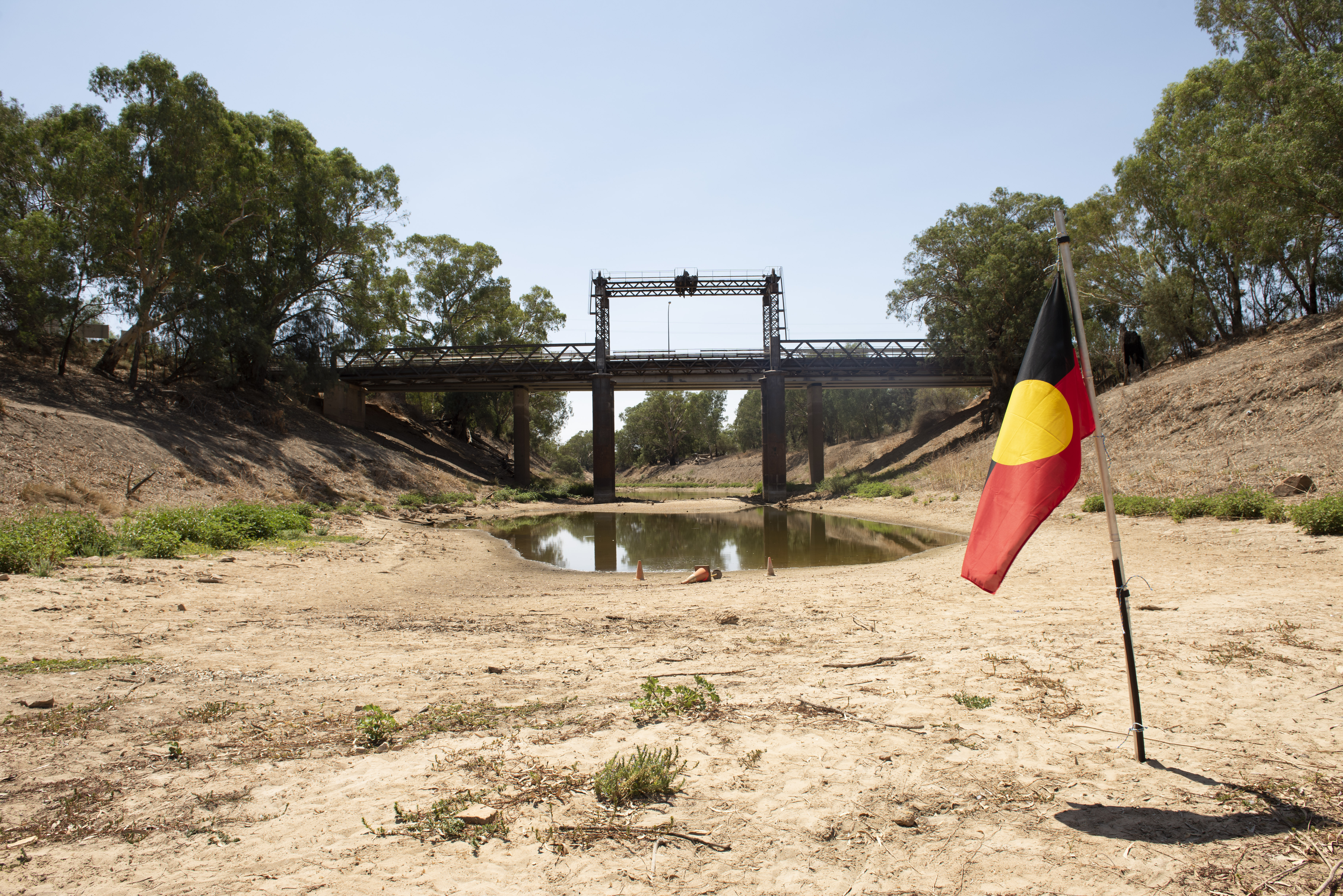 An Aboriginal flag is planted in a dry riverbed