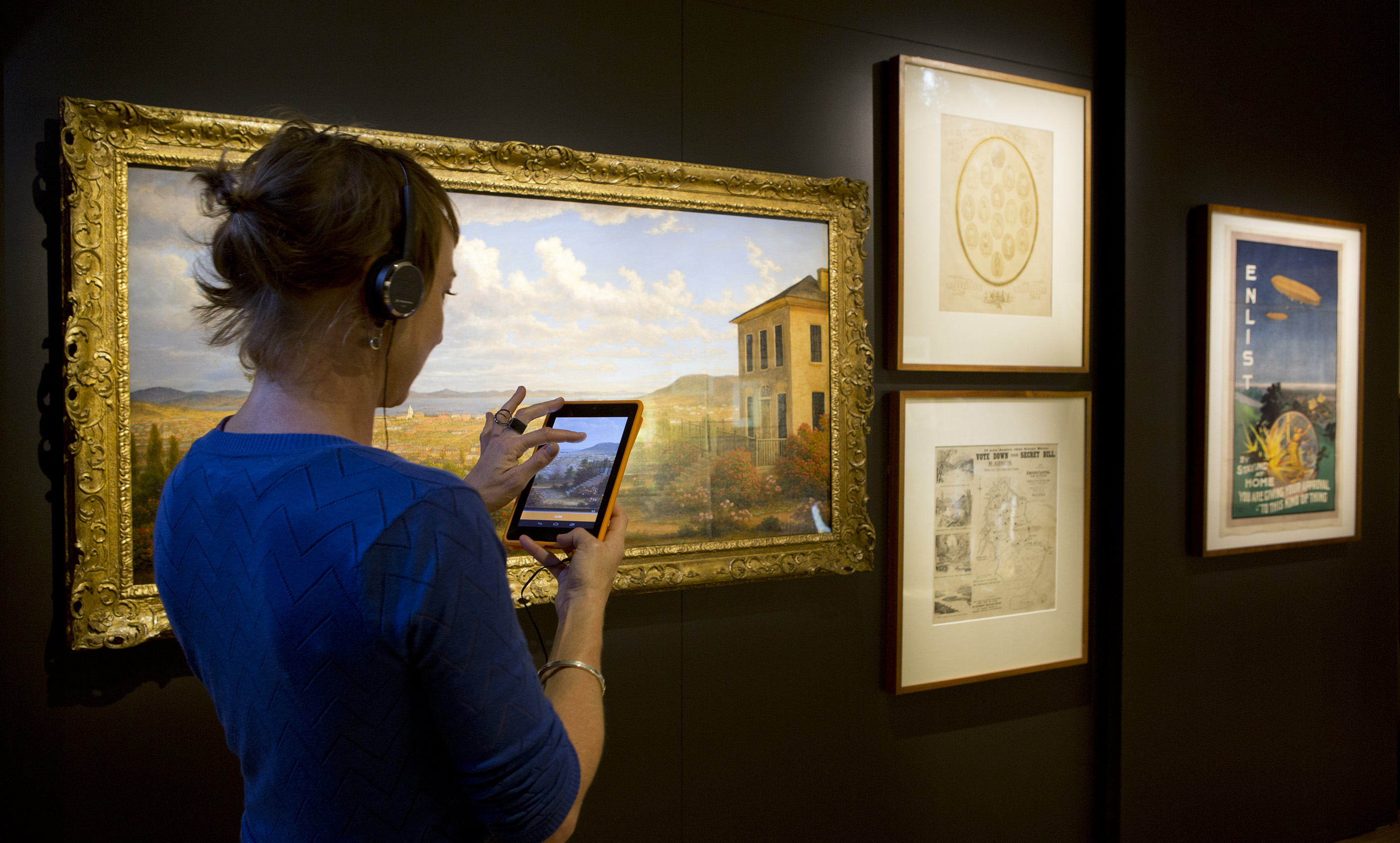 A woman uses the Library's CURIO app in front of a painting in the AMAZE gallery