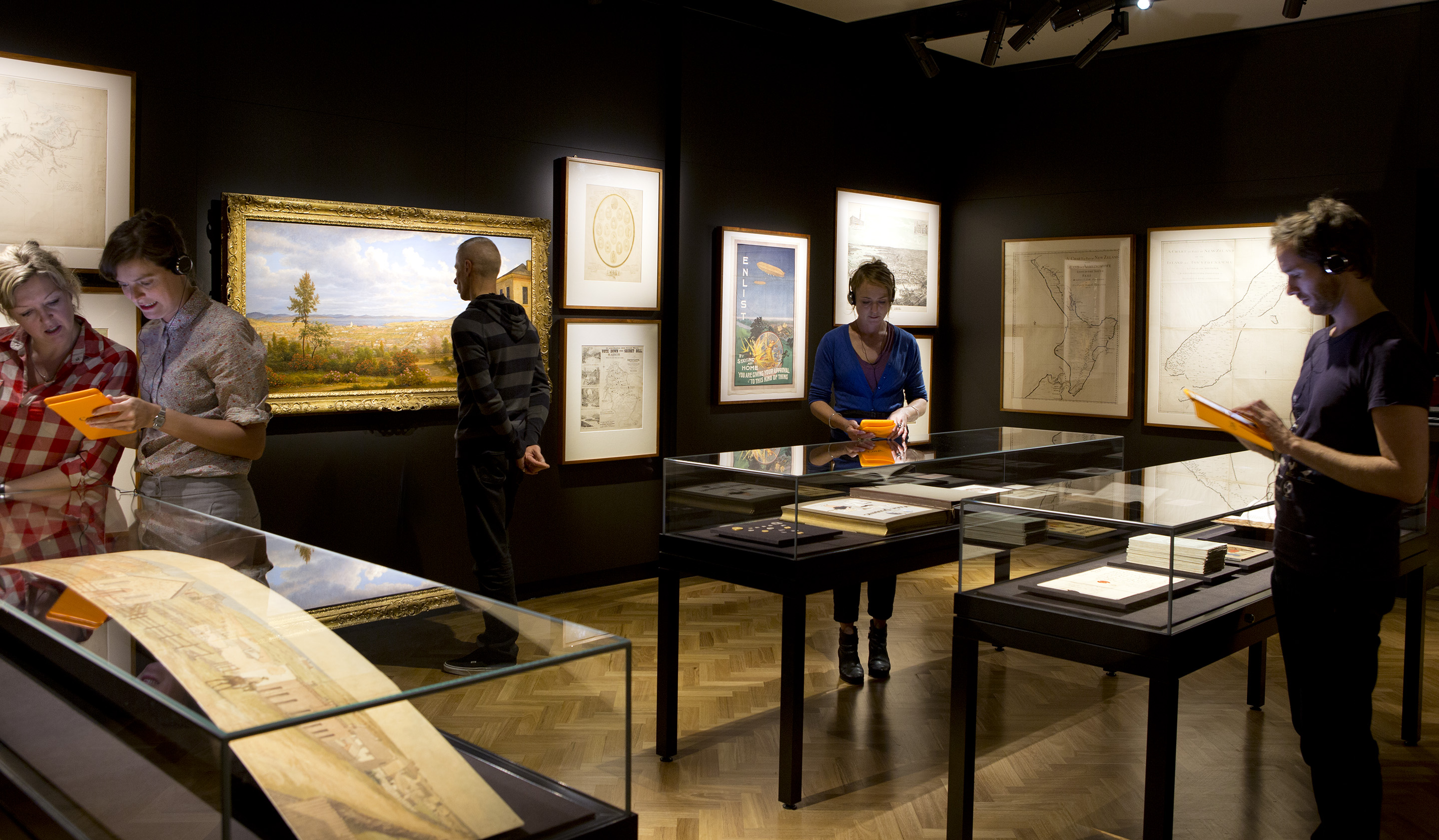 Three visitors look at a panoramic illustration on display in the AMAZE gallery
