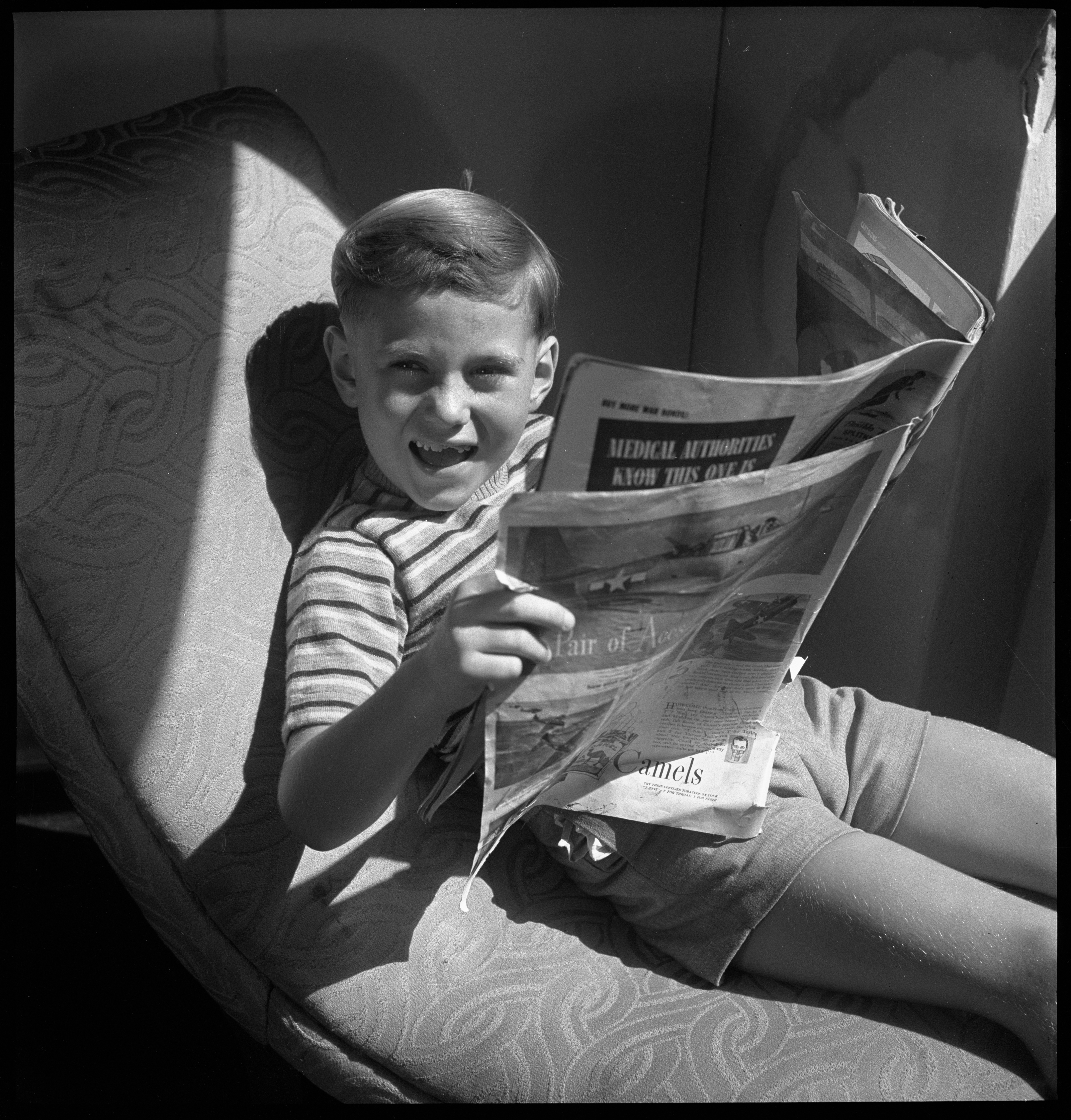 Jimmy Lee, model, 6 years old, reading newspaper, January 1946 / photographed by Max Dupain