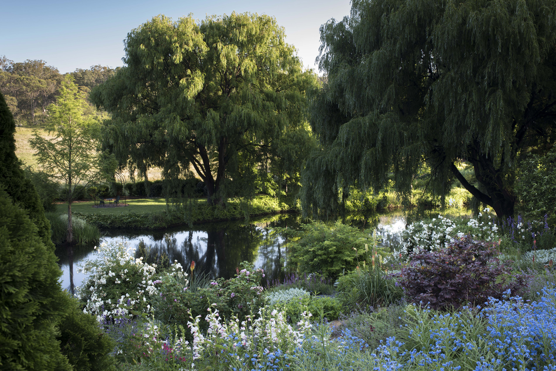 A photograph of a garden. Flowers and a lake sit in the foreground, with lush green grass backing onto a dry paddock in the background.