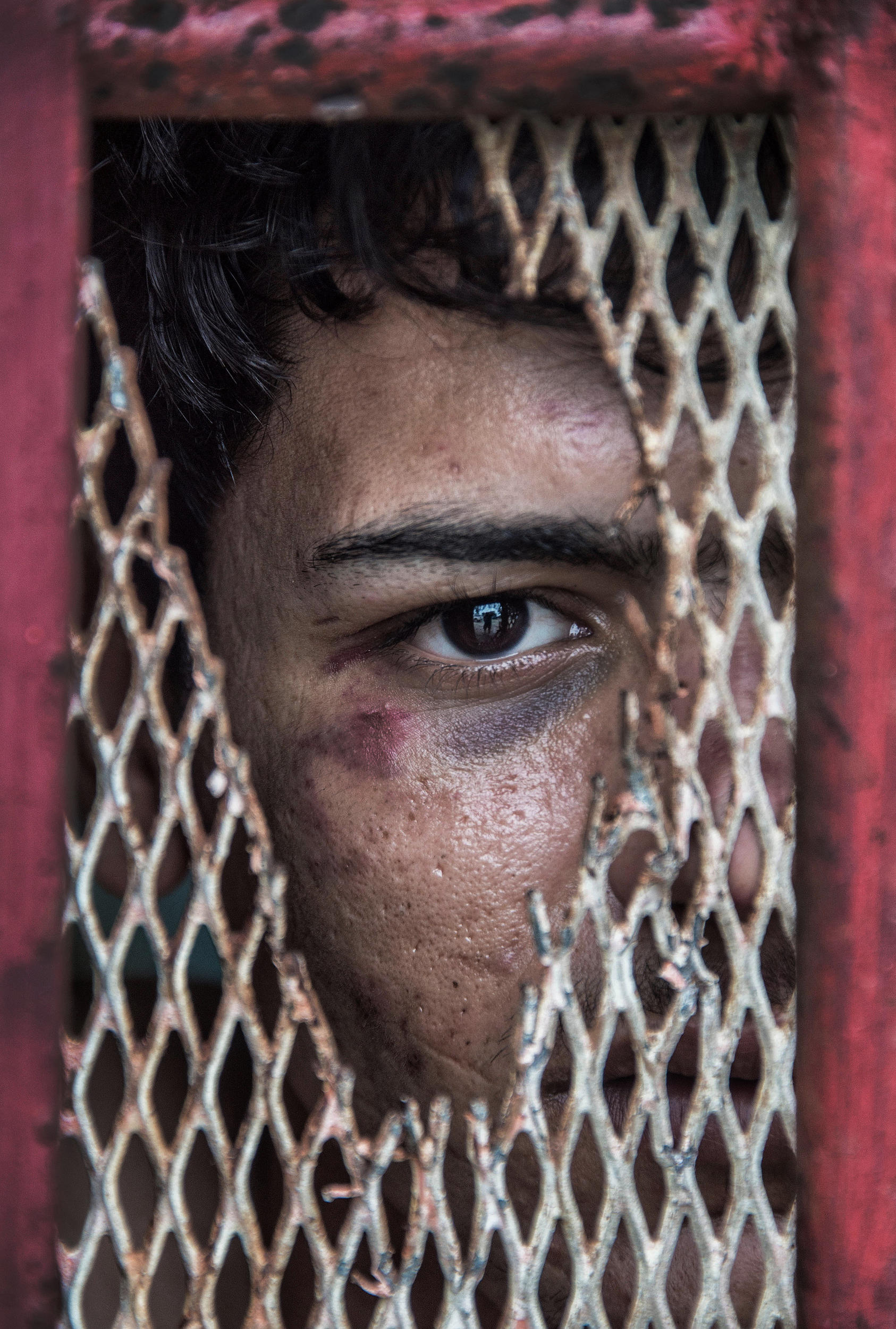 A close up colour photograph of a boy looking through the hole in a broken metal grate.