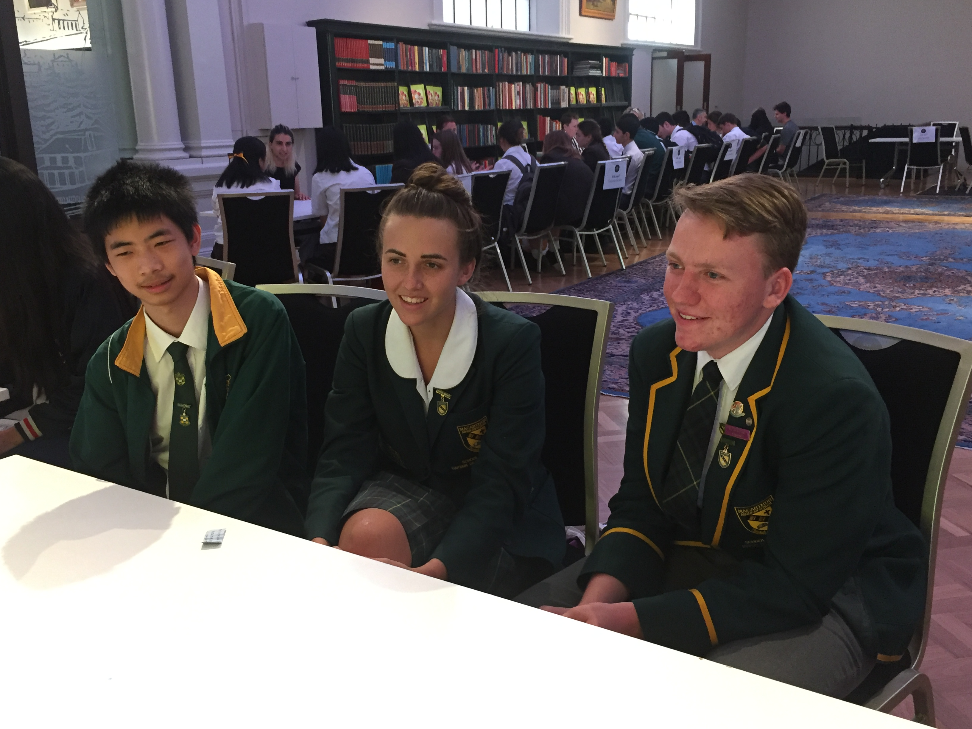 Three students sitting at a table in the Gallery Room, speaking with an 'expert' during the Speed Date an Expert session as part of the History Extension Seminar Day.