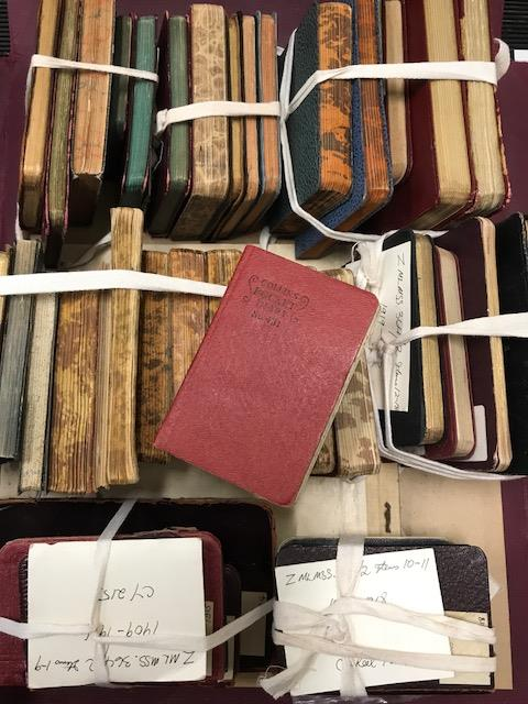 stacks on small books tied with cloth string.