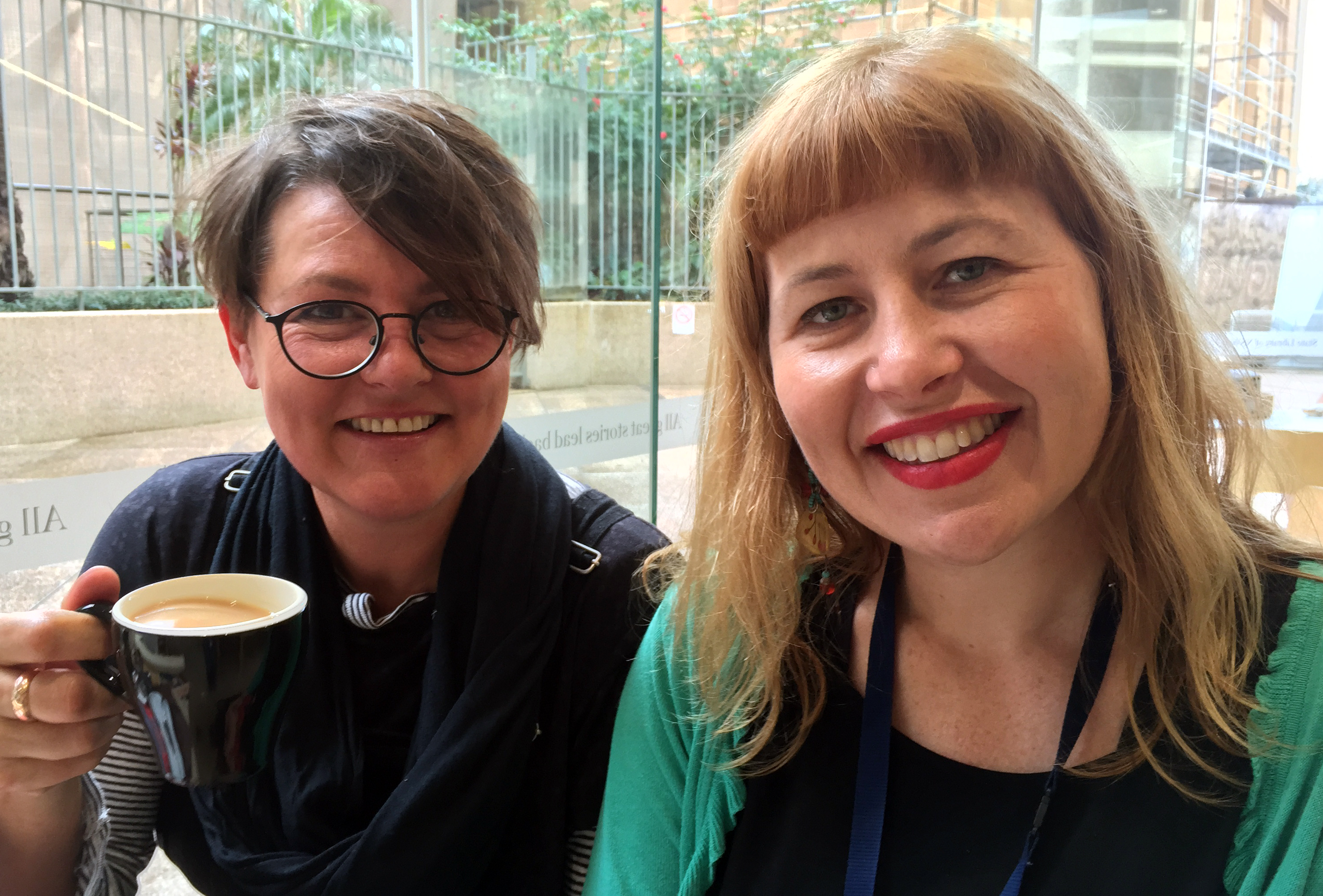 Two women sit side by side smiling at the camera - one holds a cup of tea.