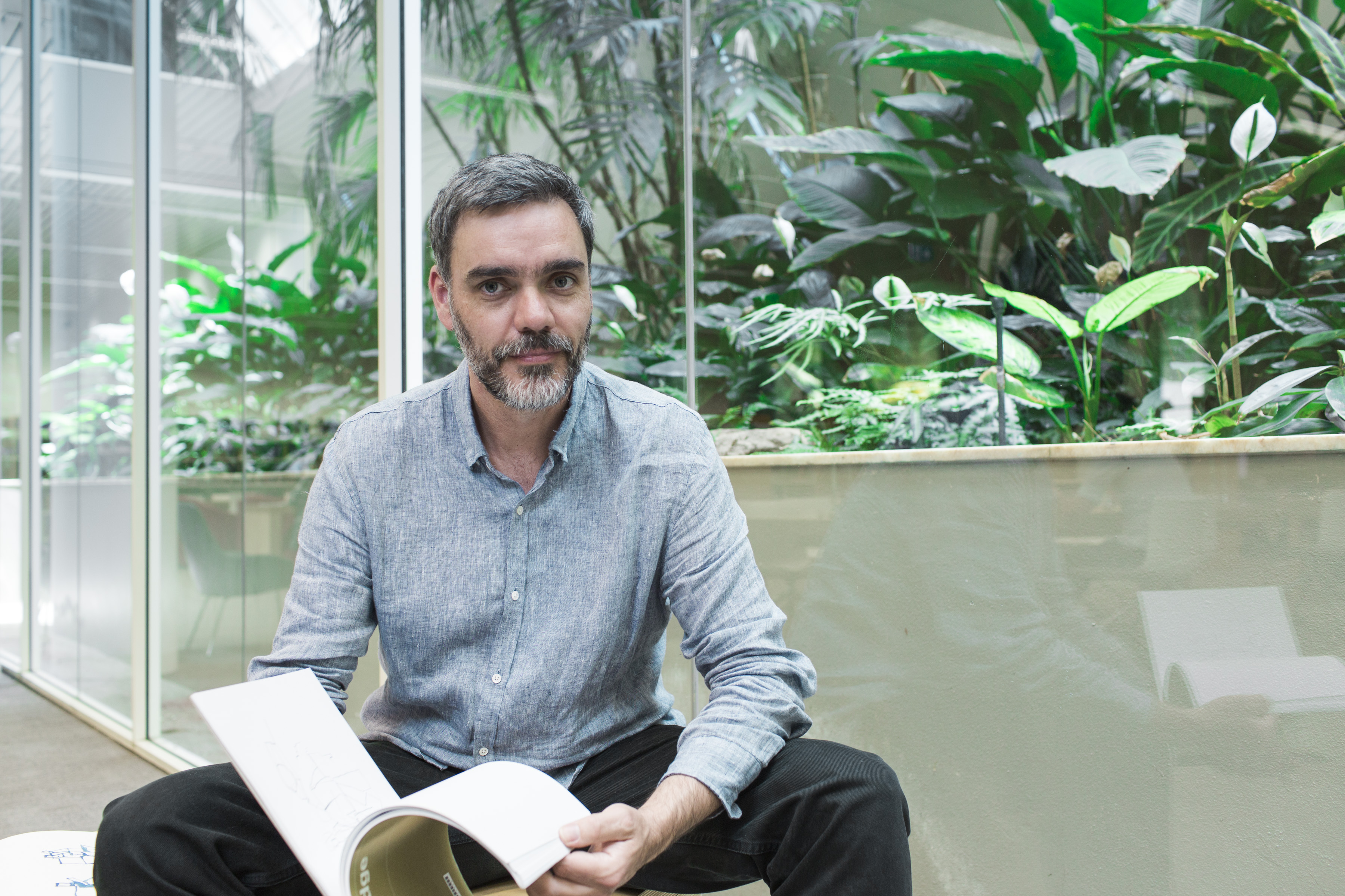 Joe Frost, State Library 'artist in residence', sitting with a book in hand, in the Governor Marie Bashir Reading Room.