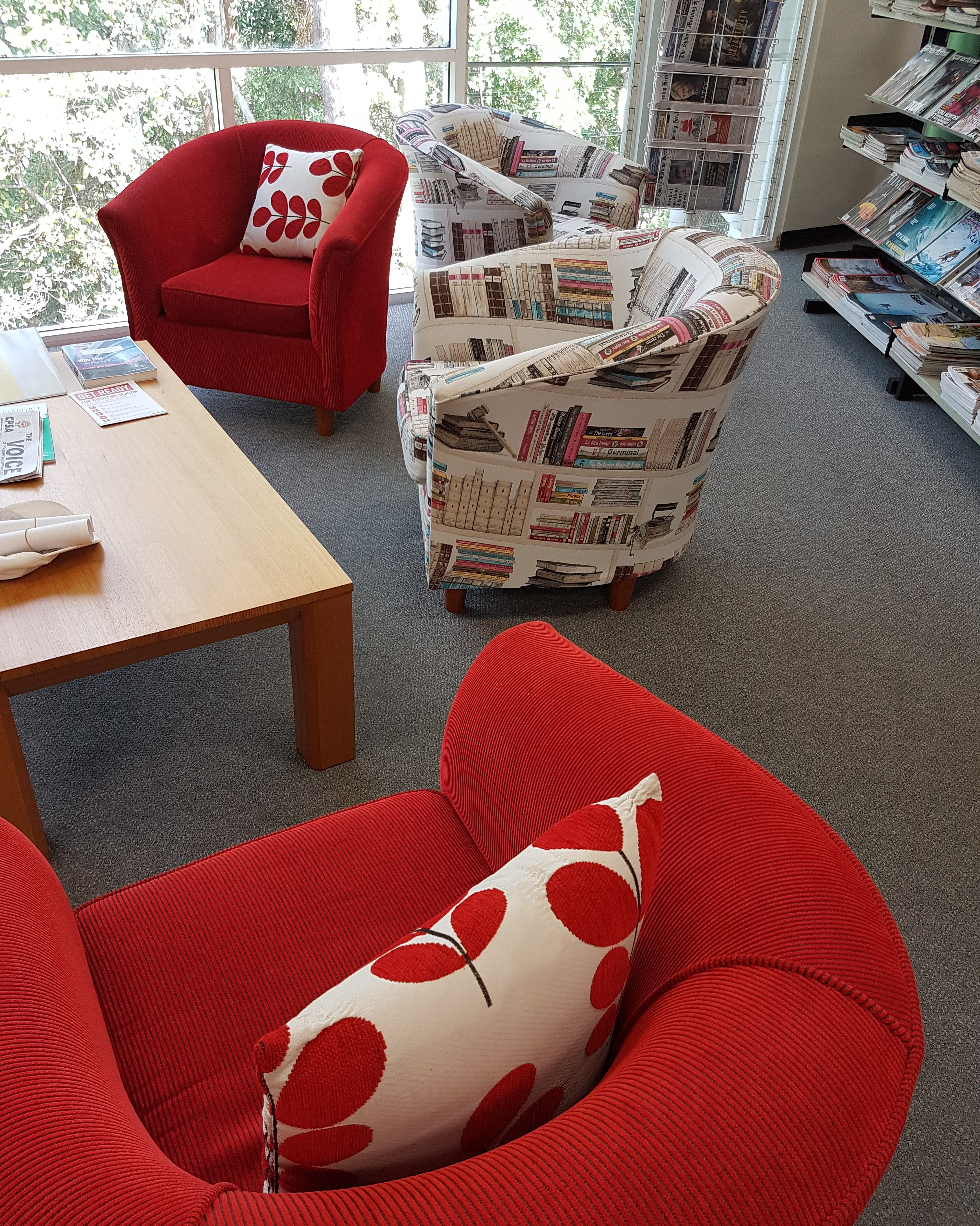 Lounge chairs covered in red, and book print fabric in Nambucca Library