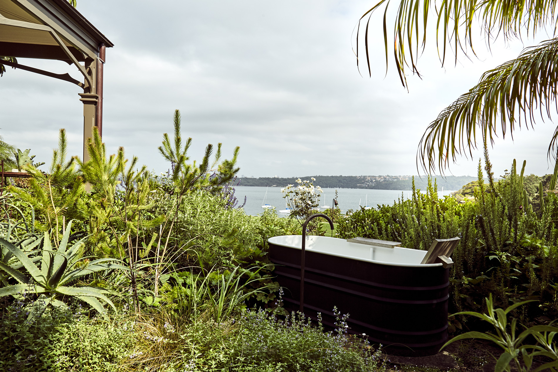 A photograph of a bathtub sitting in a garden, surrounded by plants and grasses. The ocean can be seen beyond the garden and the edge of a house sits in the left of the image.