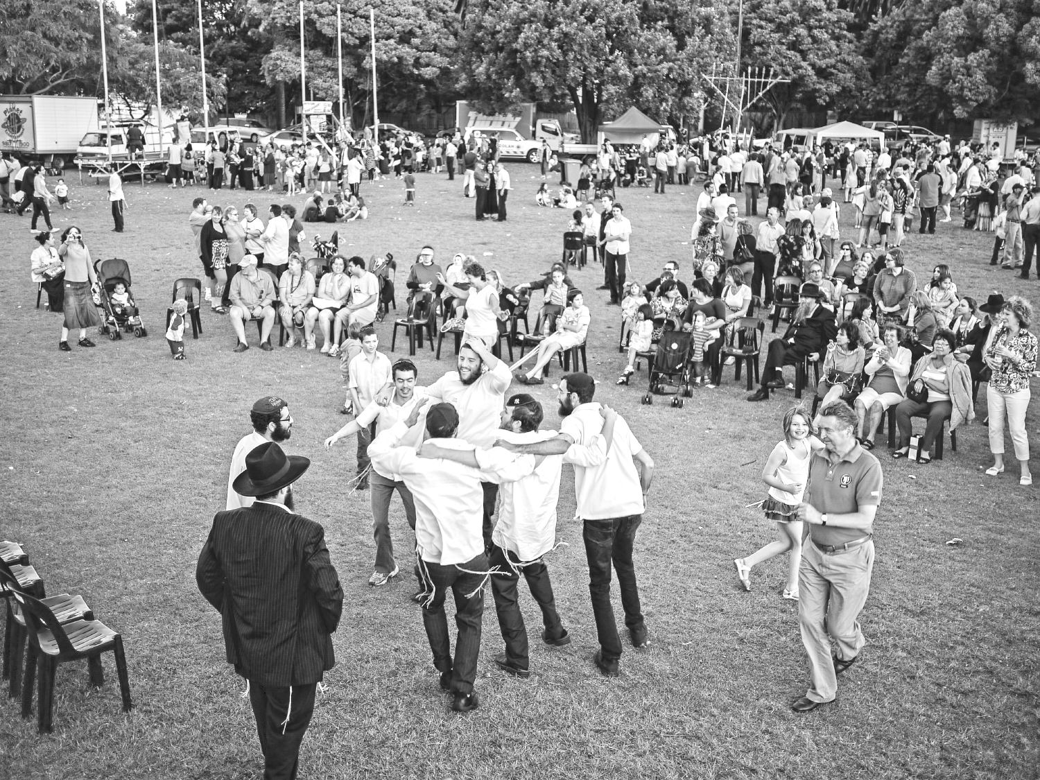 Men and women dance in a park at a community event with a crowd of people watching on.